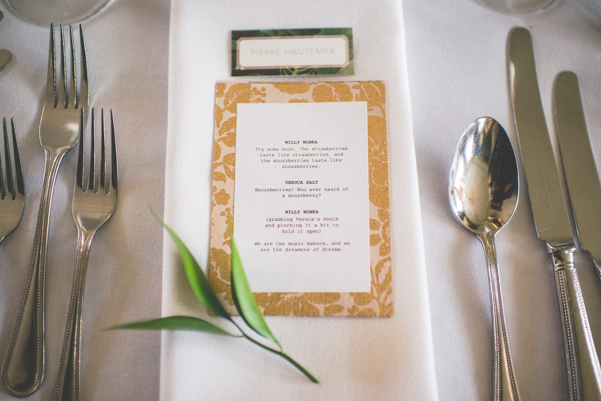 A close up shot of a guest's place setting, showing an individual film quotation - this one is from Willy Wonka and the Chocolate Factory