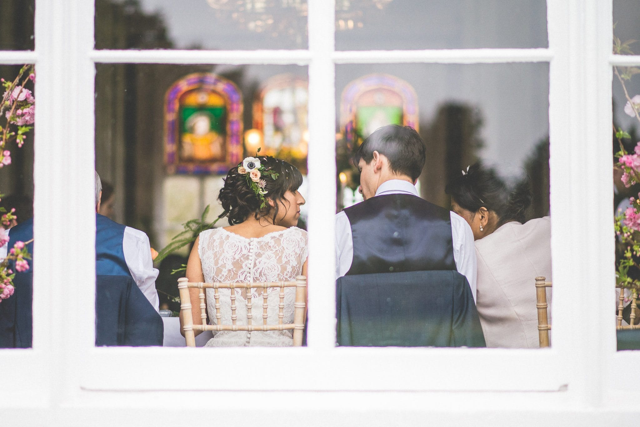 A shot looking in from outside the window, behind Jasmin and Andy seated at the top table