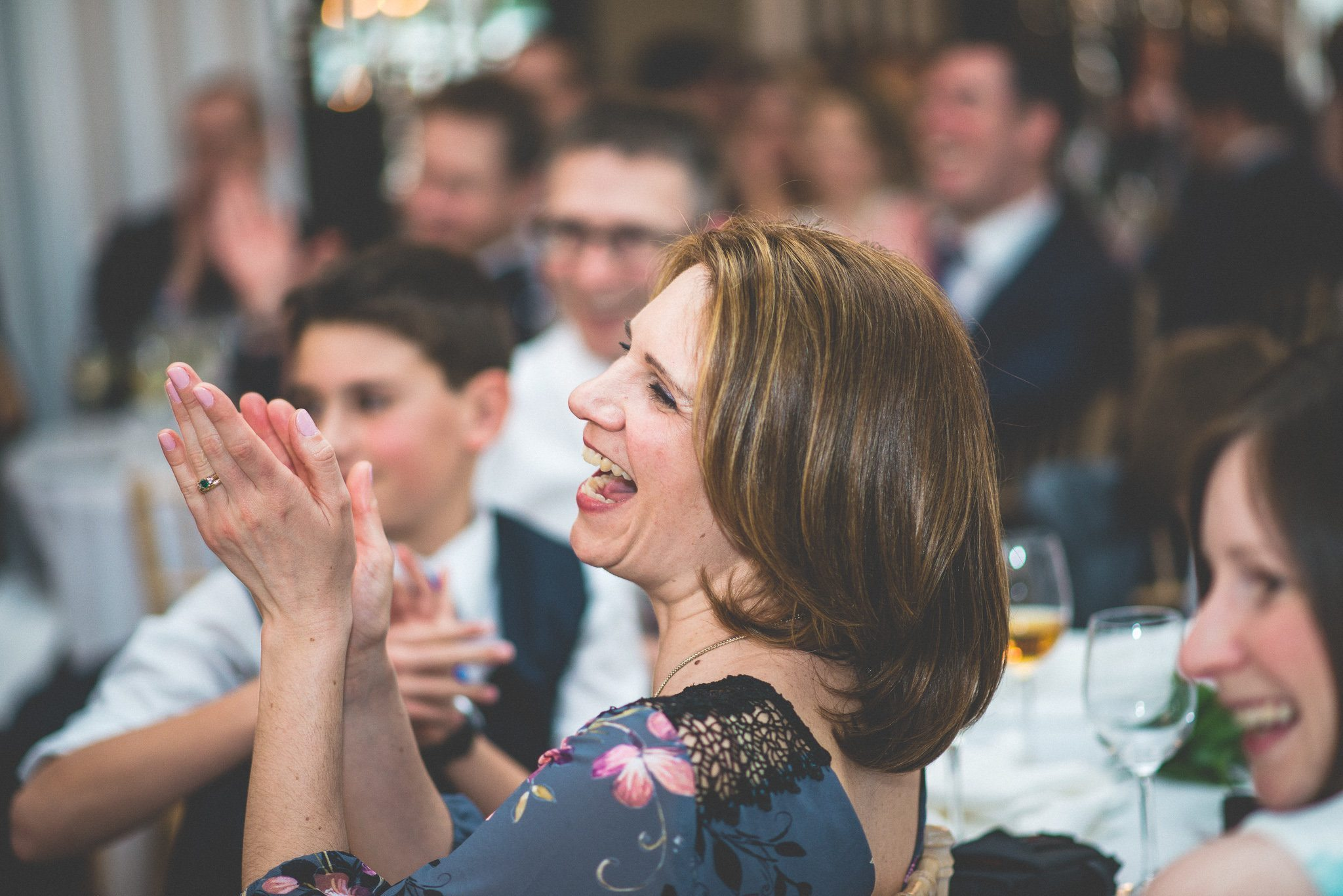 A close up of one of the guests laughing and applauding