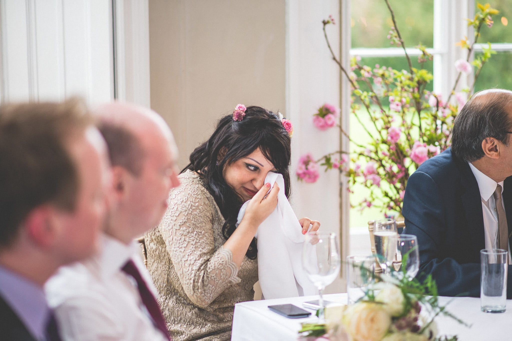 A bridesmaid in a gold dress wipes her eyes with a napkin as things get emotional
