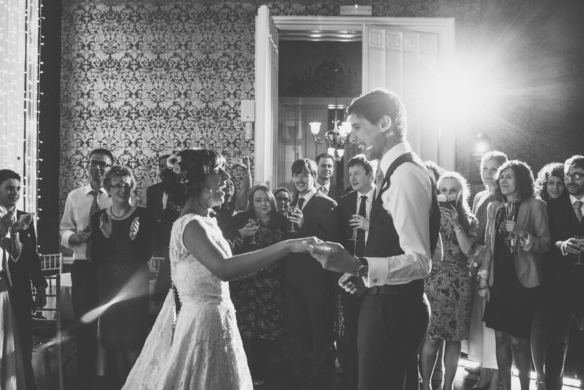A black and white shot taken during the couple's first dance, both are shown bursting out laughing as they take to the floor