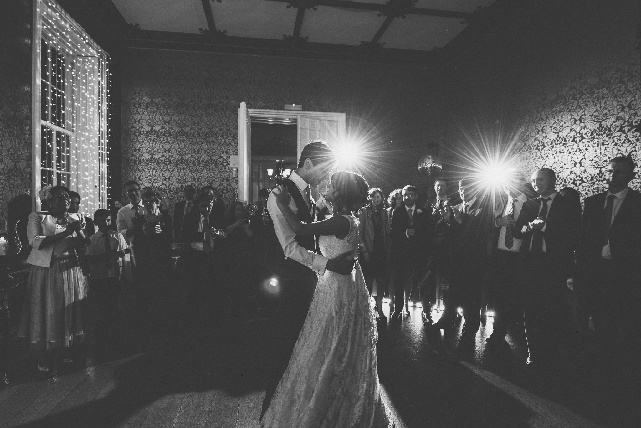 A black and white shot of the couple holding each other close during their first dance