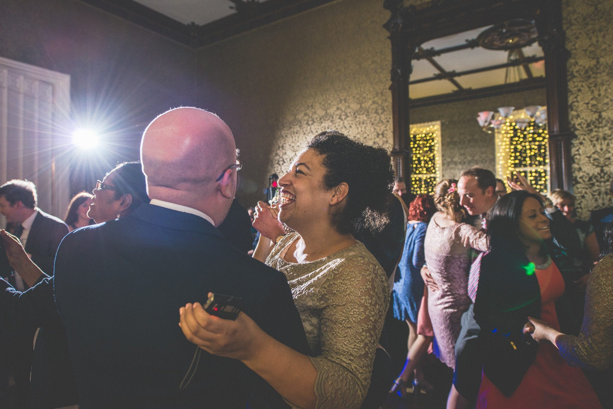 One of the bridesmaids dances with one of the groomsmen as the floor fills up