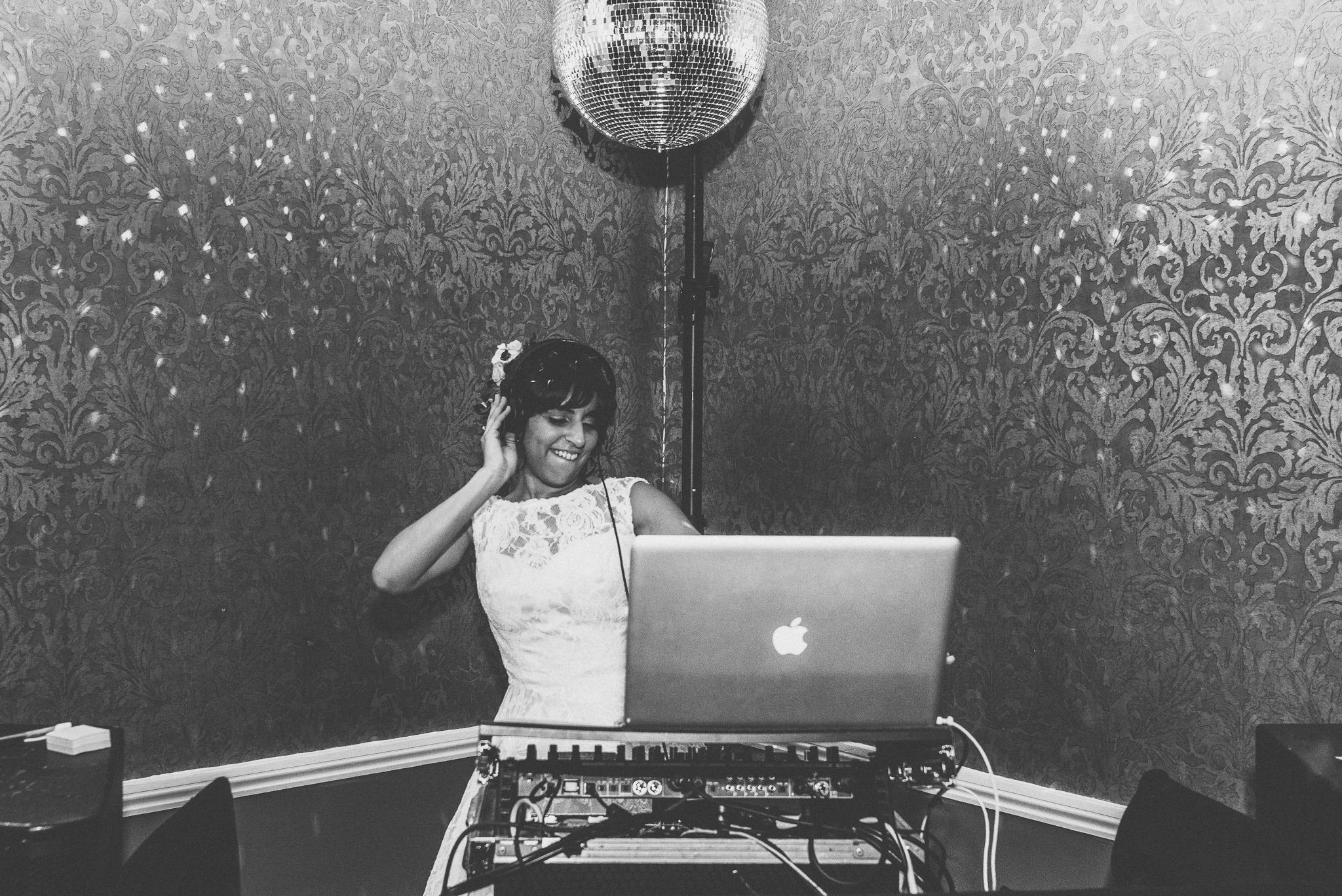 The bride plays DJ! Jasmin stands in the booth with headphones on, underneath a mirror ball.