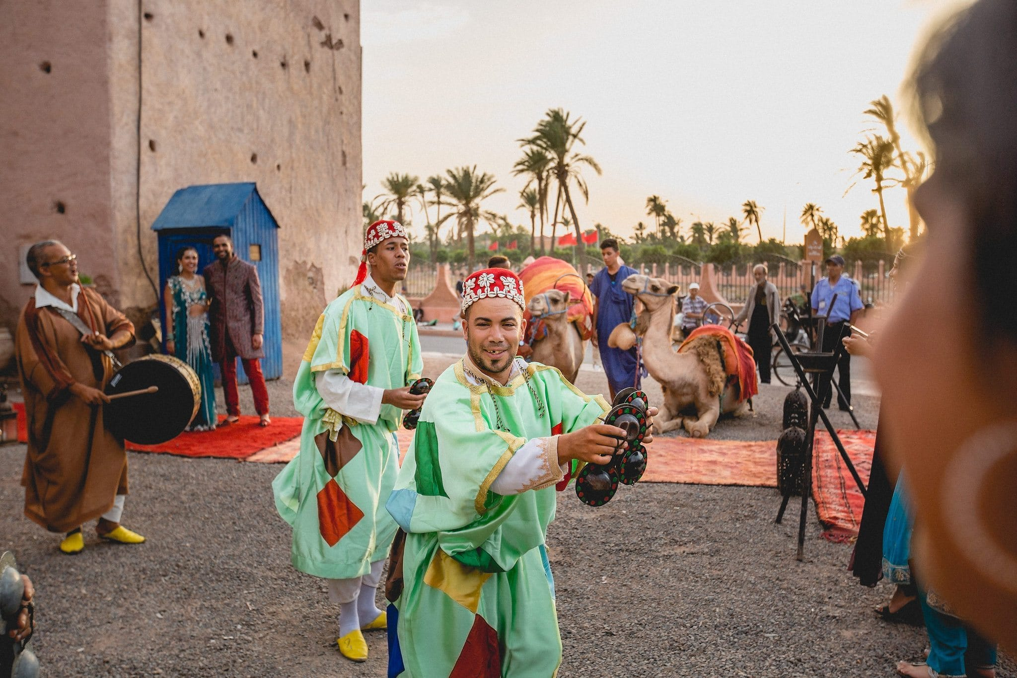 Moroccan musicians dance and play instruments as wedding guests arrive