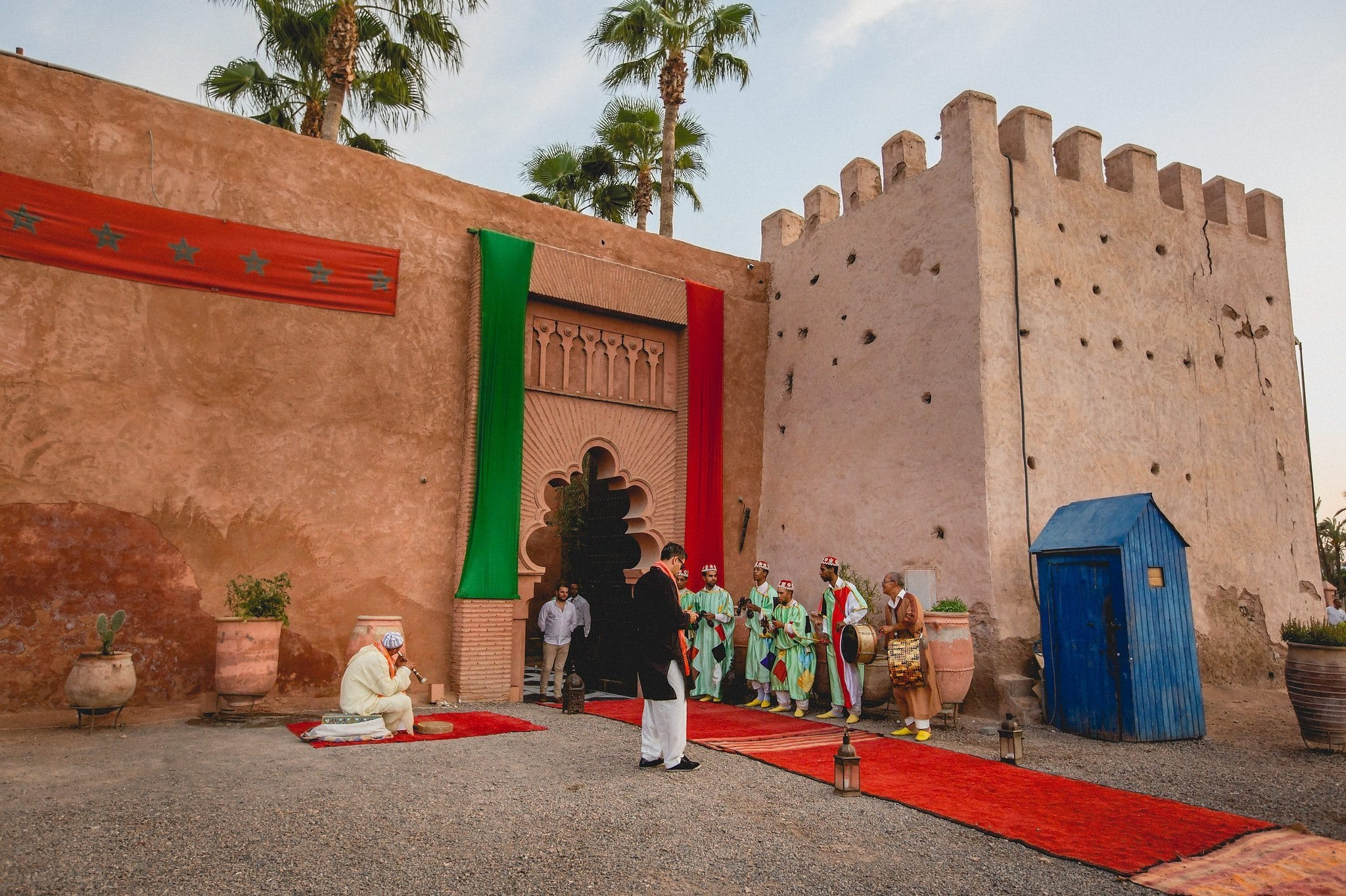 Palais Soleiman in Marrakech with red and green banners and palm trees in the back