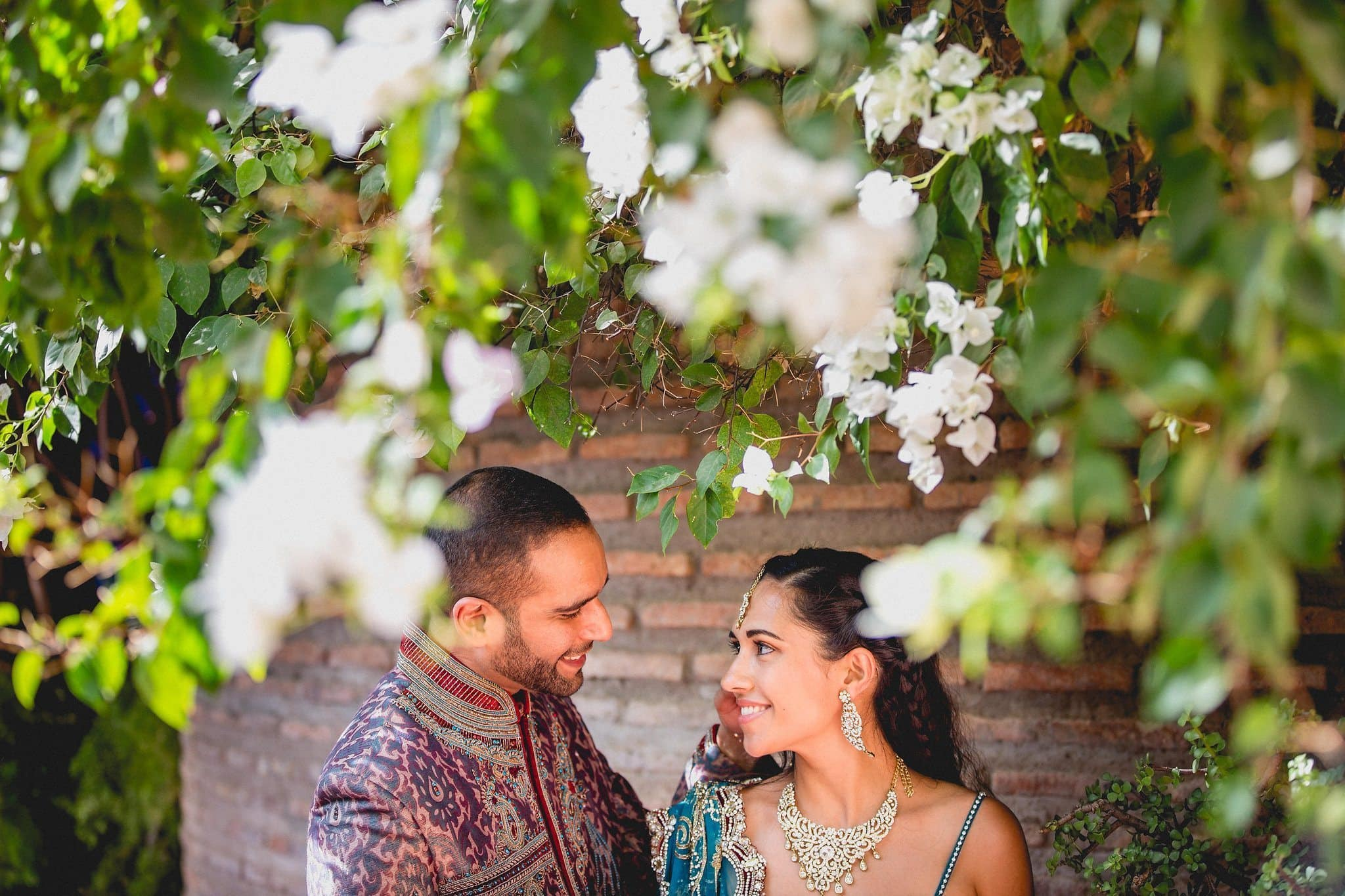 Indian bride and groom gaze at each other under white blooms at the Marrakech Majorelle Gardens