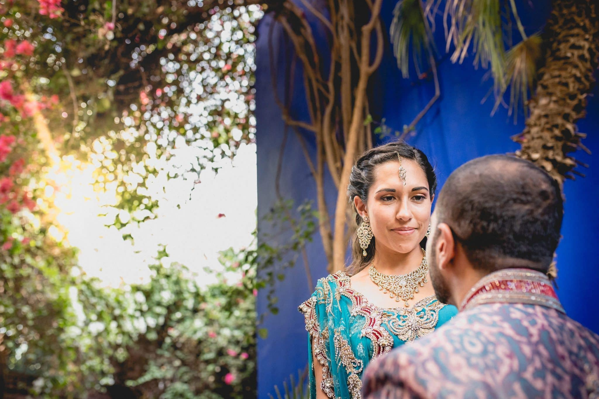 Indian Bride looking at her groom with a sun flare and the blue wall at the Majorelle Gardens