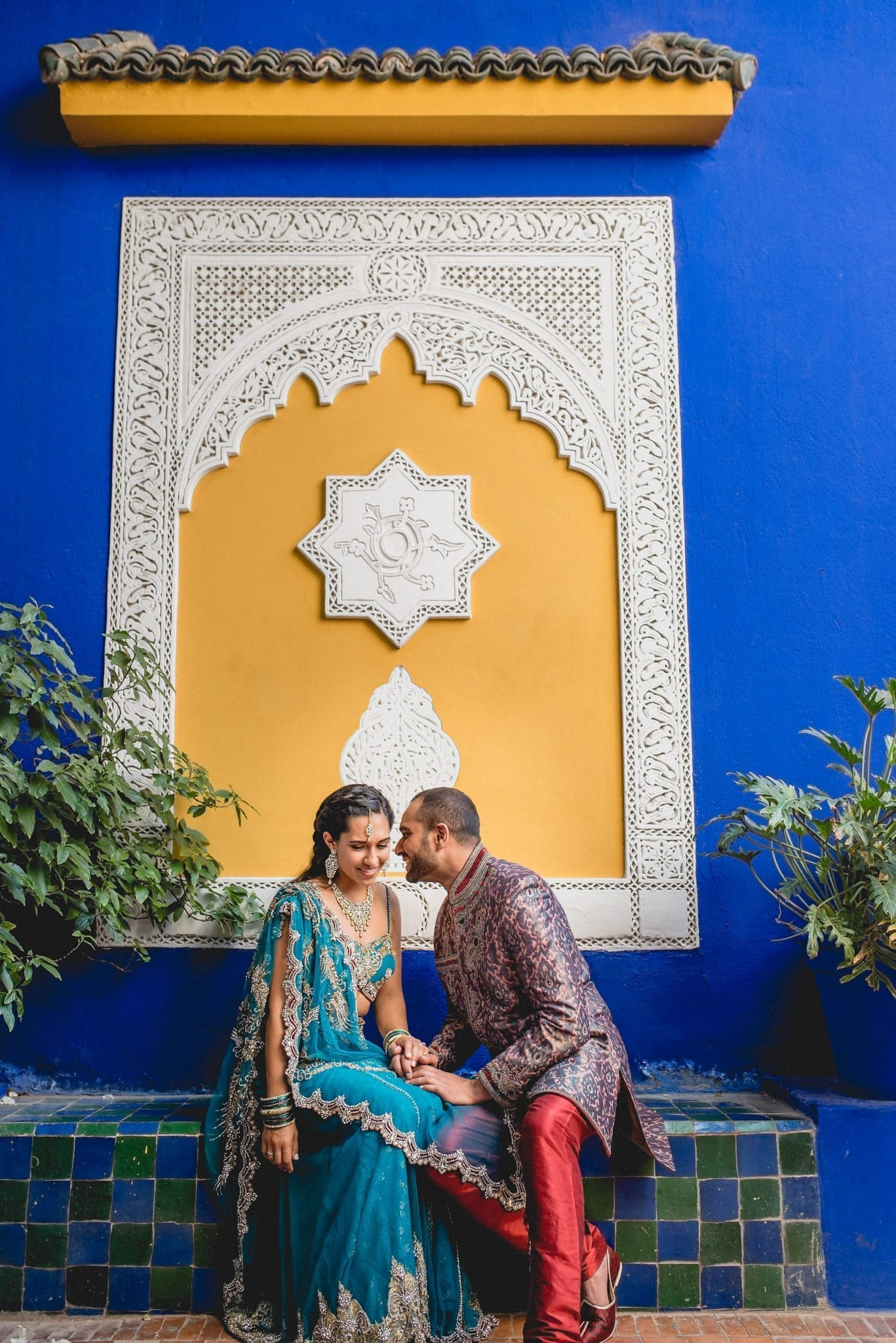 Asian bride and groom sit against a blues and yellow wall of the Majorelle Gardens