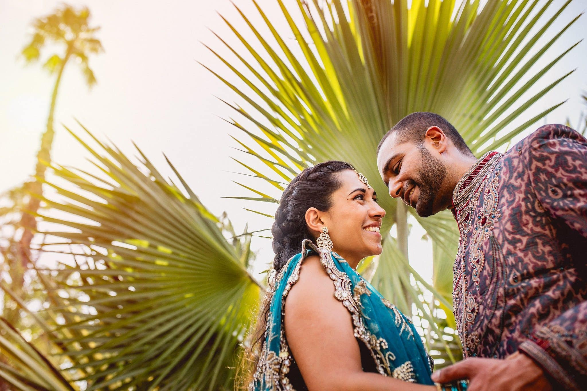 Asian bride and groom smile at each other framed by a large palm tree leaf in Marrakech