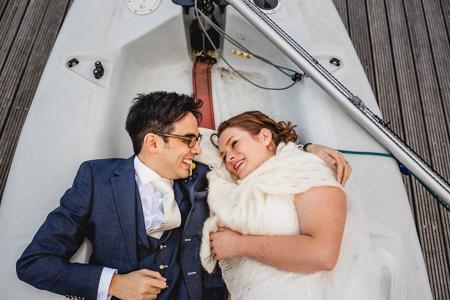 Bride and groom lying in a boat at their West Reservoir Wedding | Start Wedding Planning