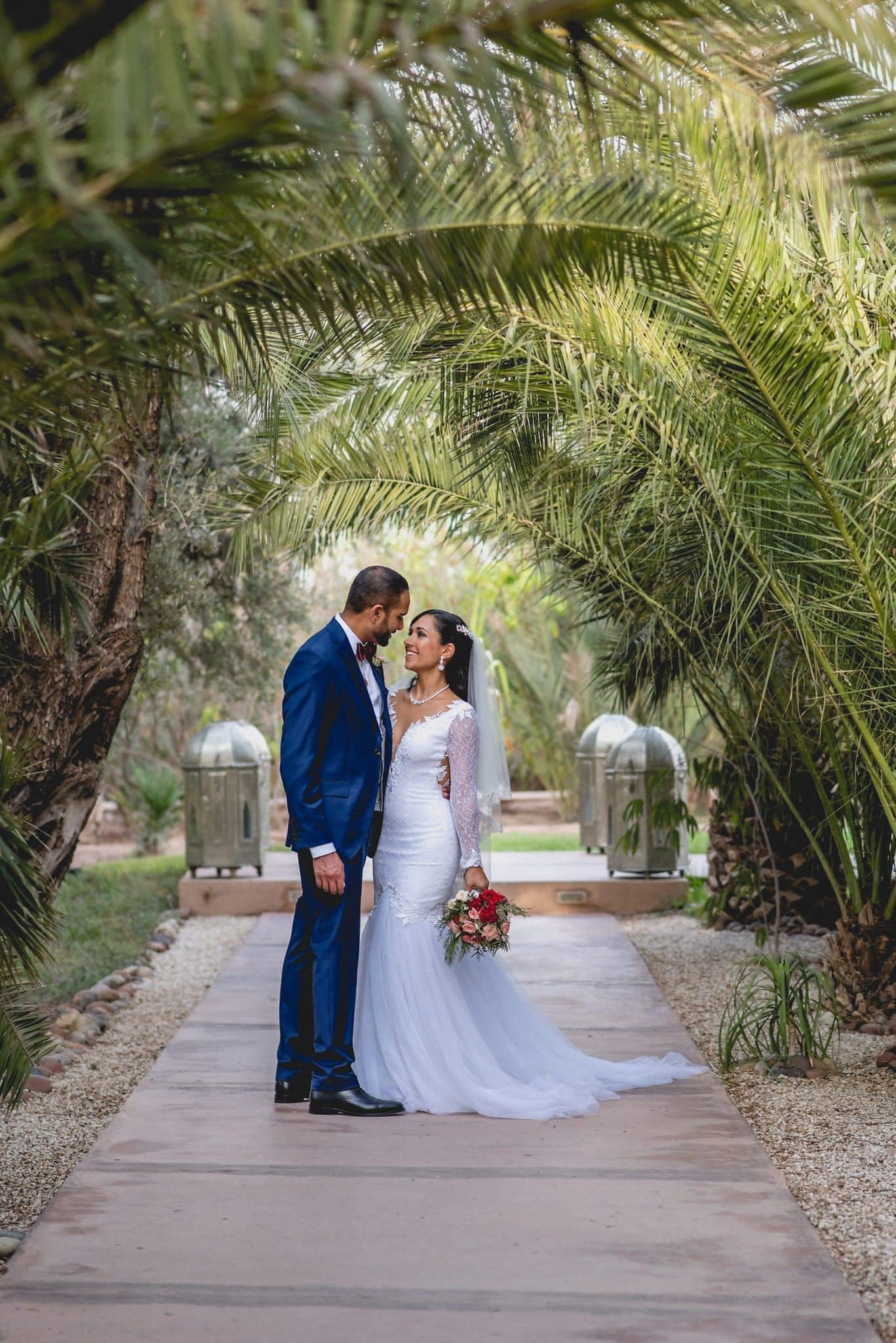 The couple pose in the grounds of the Ksar Char Bagh, under a natural arch formed by palm trees