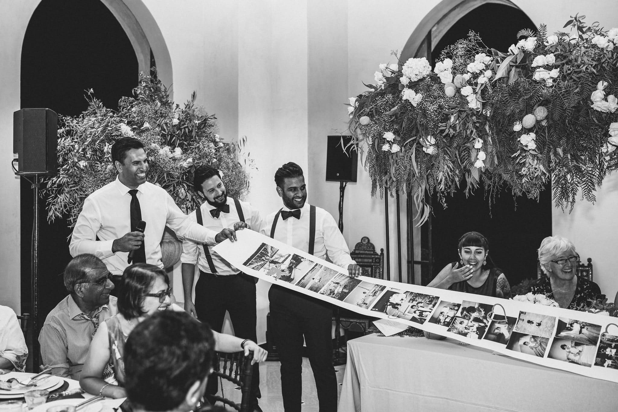 Groomsmen unroll a paper photo roll showing the funny story of the groom