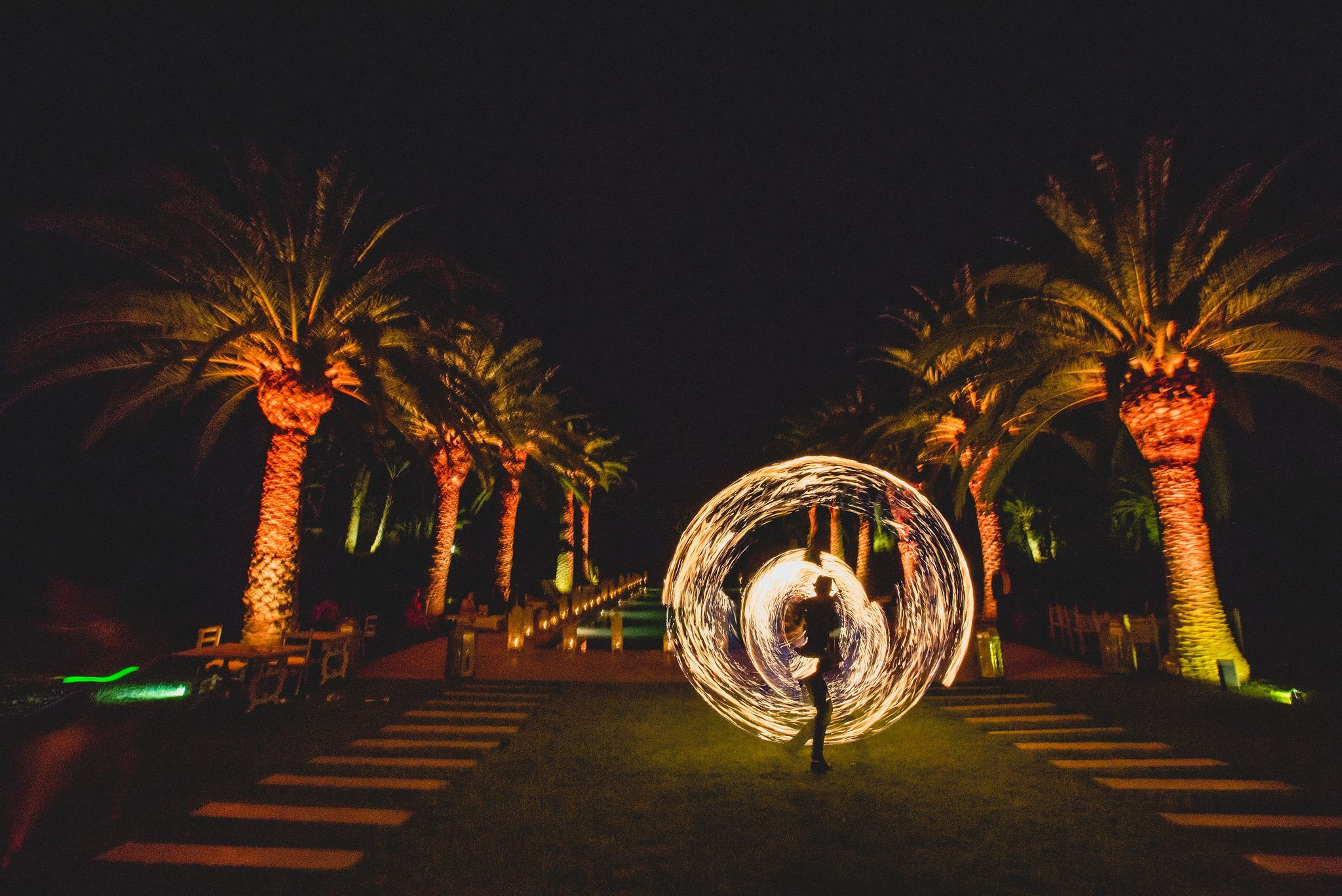 A fire dancer spins fire poi outside the venue among the palm trees
