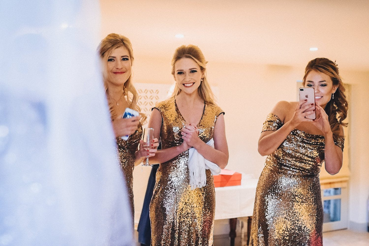 Three bridesmaids wearing gold sequinned dresses get a first look at the bride in her dress