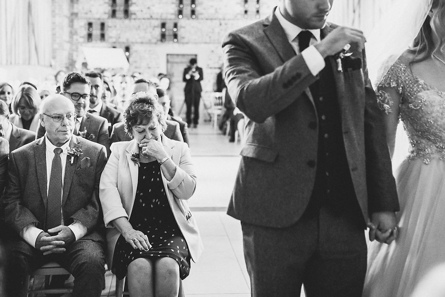 A black and white shot of an emotional mum during the wedding ceremony