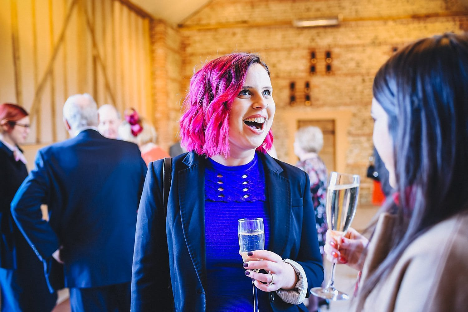 A female guest with bright pink hair chats to a friend while holding a glass of fizz