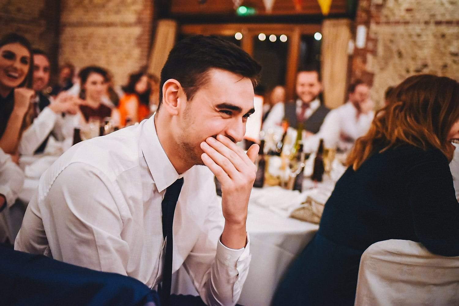 A male guest leans forward and laughs during the speeches