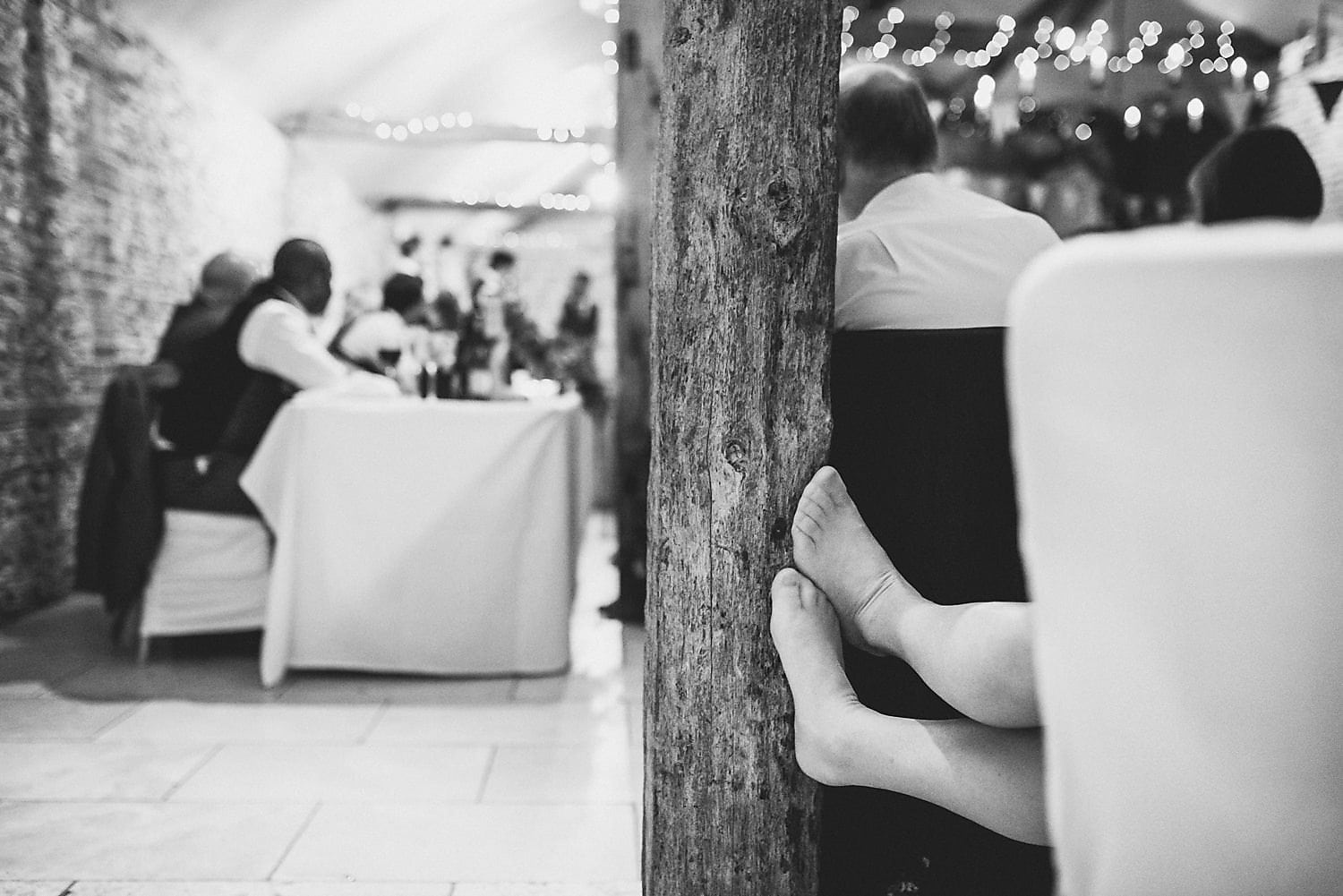 Wedding guests putting her feet up at Upwaltham Barns during the wedding speeches