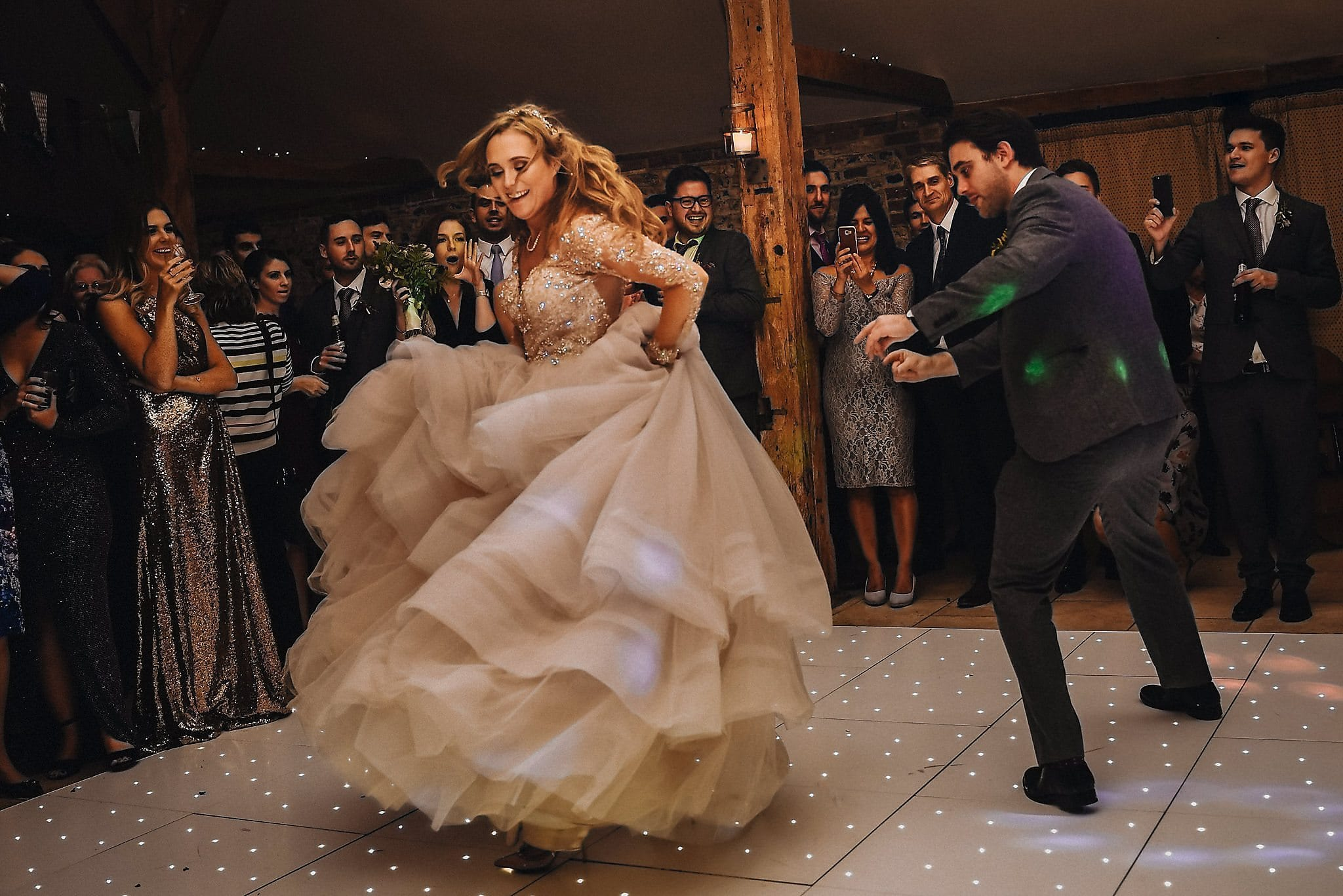 Bride and groom dancing a fun routine at their Autumnal Upwaltham Barns Wedding