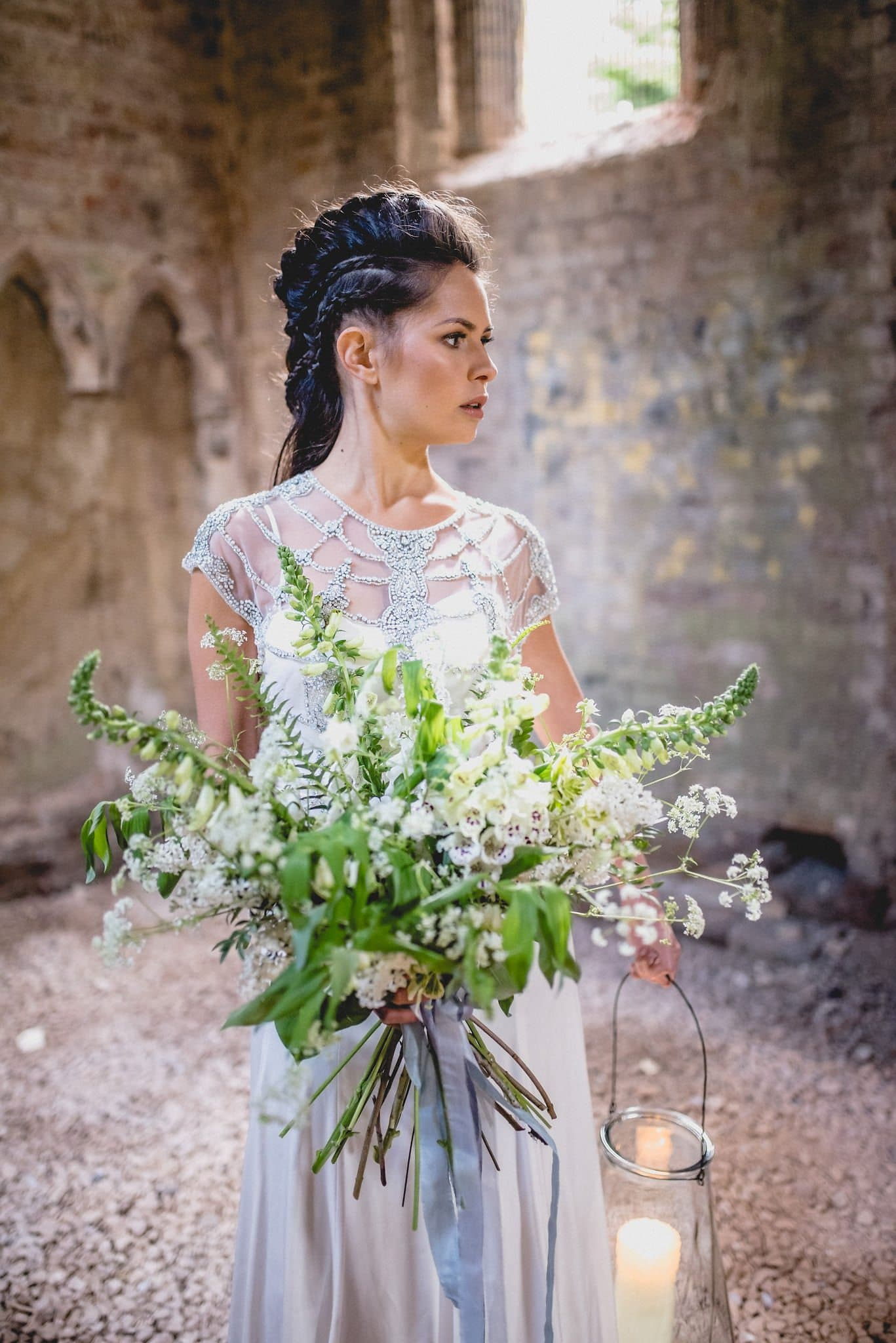 Bride with elaborately braided hair carries large bouquet and storm lantern with candle