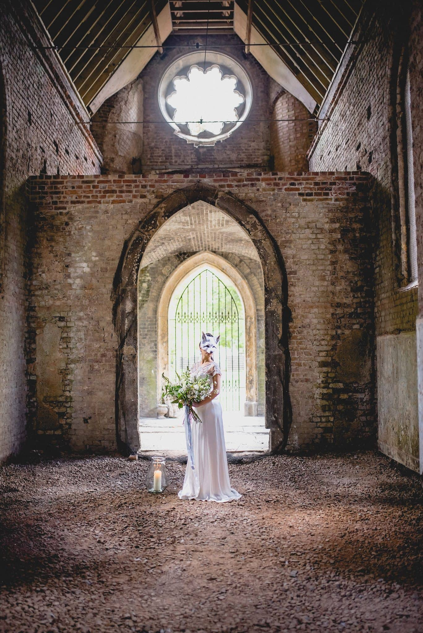 Bride in Catherine Deane standing in the ruined Gothic chapel at Abney Park cemetery