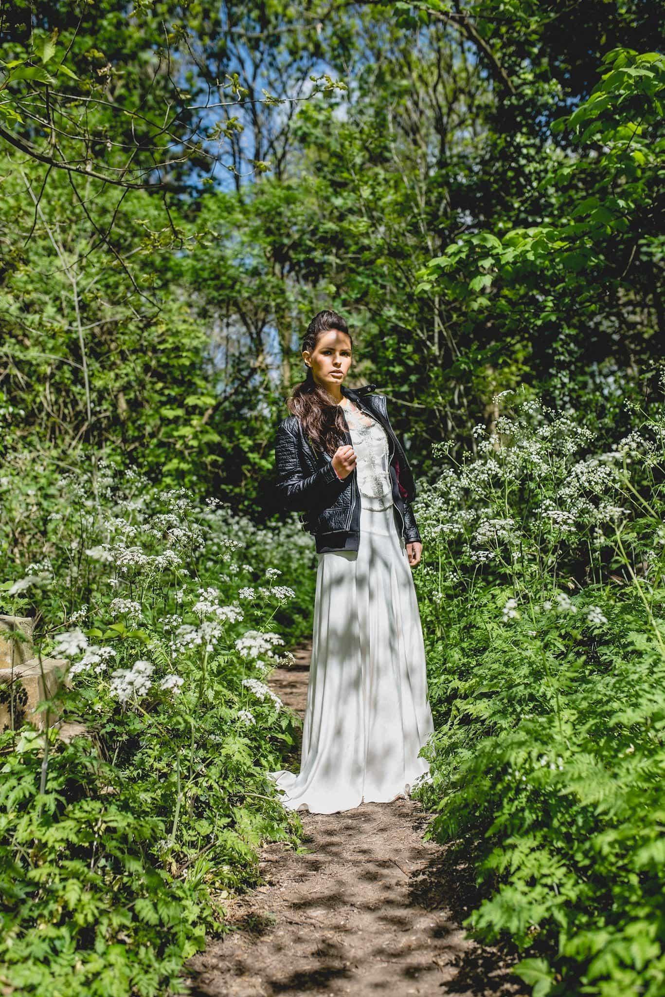 Bride in Catherine Deane separates with leather jacket among wildflowers in Abney Park