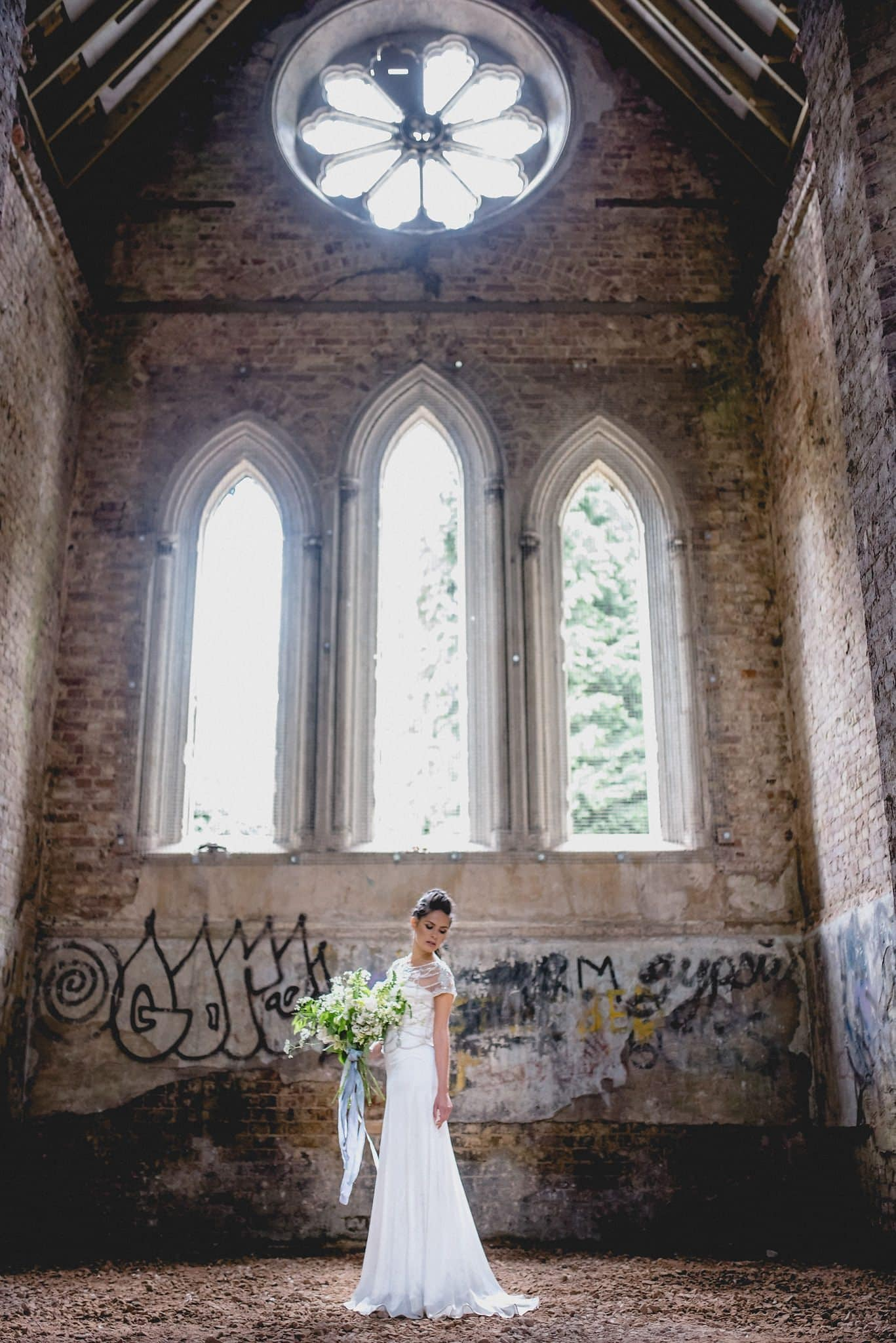Sunlit bride in the rustic ruined Gothic chapel in Abney Park