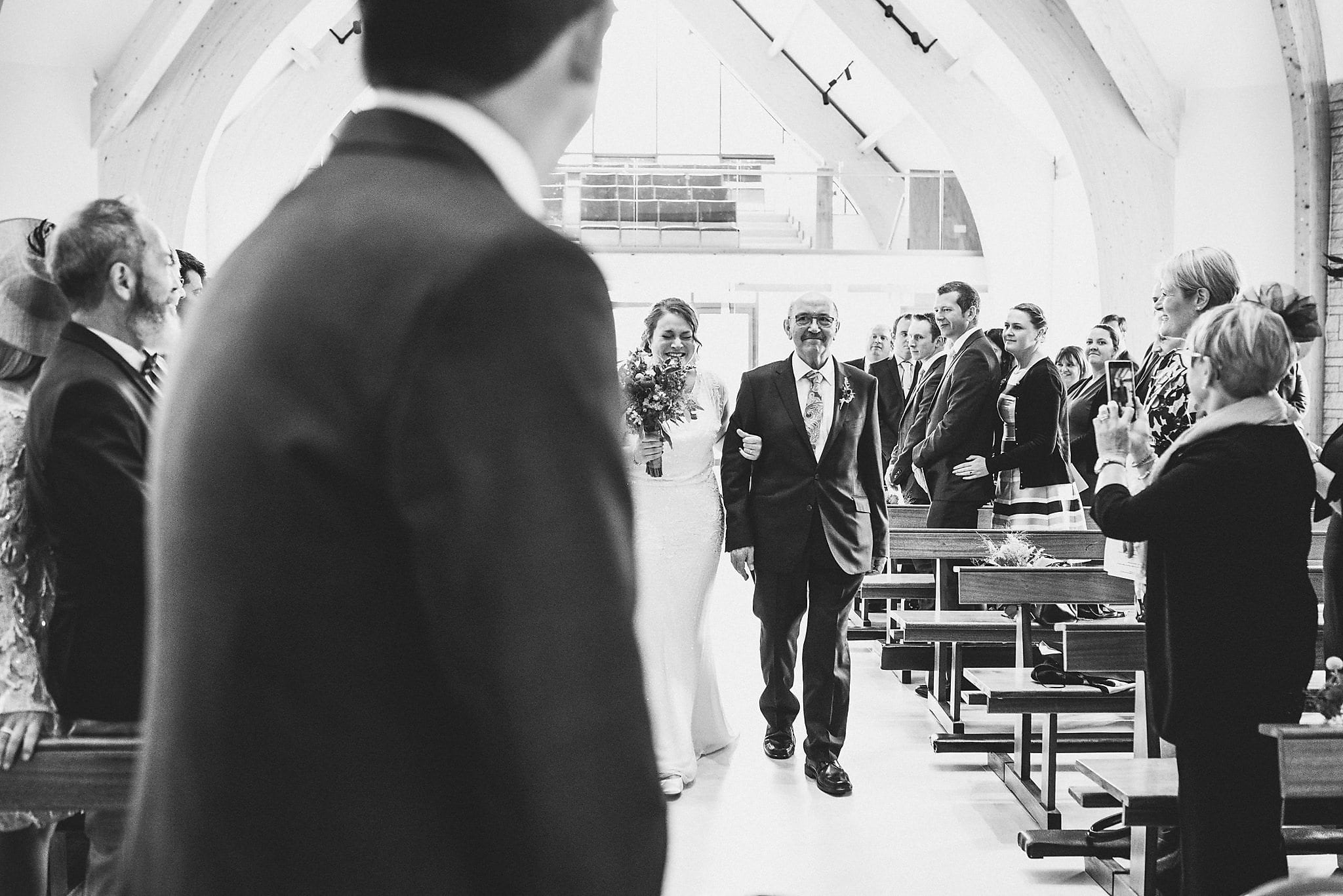 Bride walking down the aisle and laughing with happiness