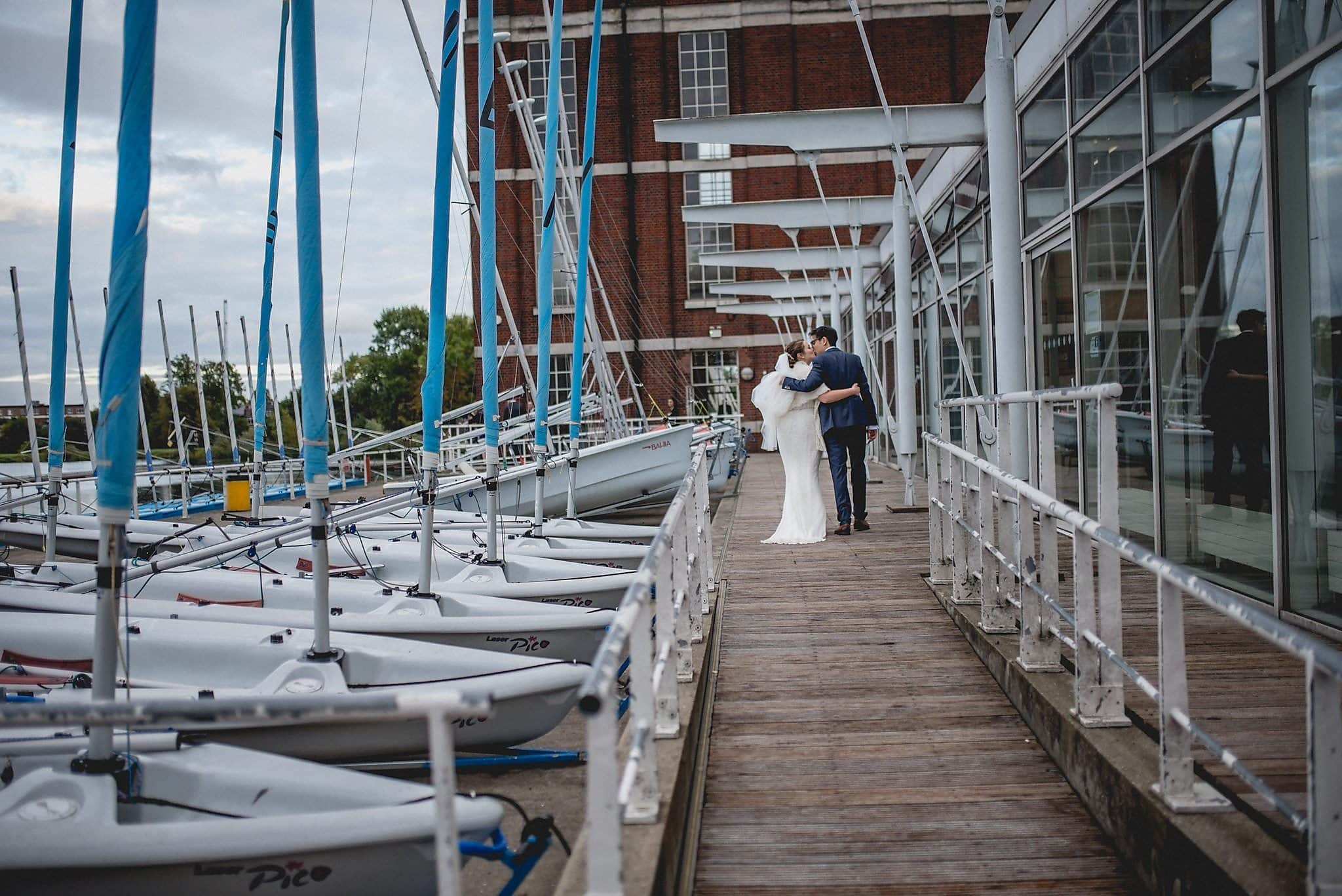 Bride and groom walking up to the West Reservoir Centre for their wedding reception framed by boats and boat masts