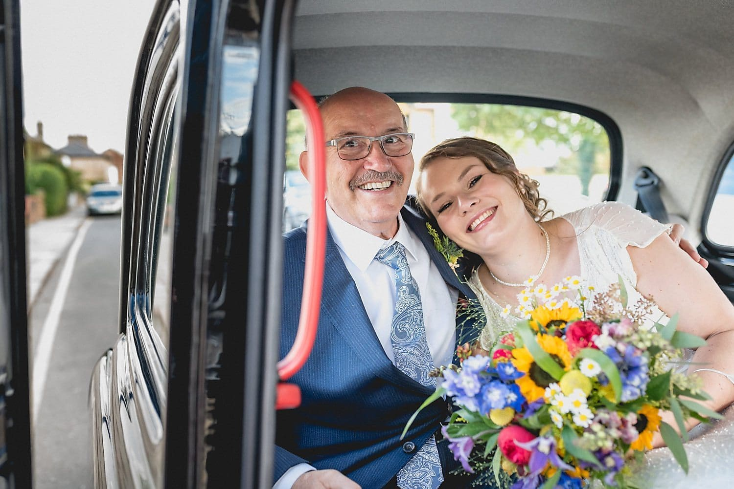 The bride and her father arrive at the church in the back of a black cab