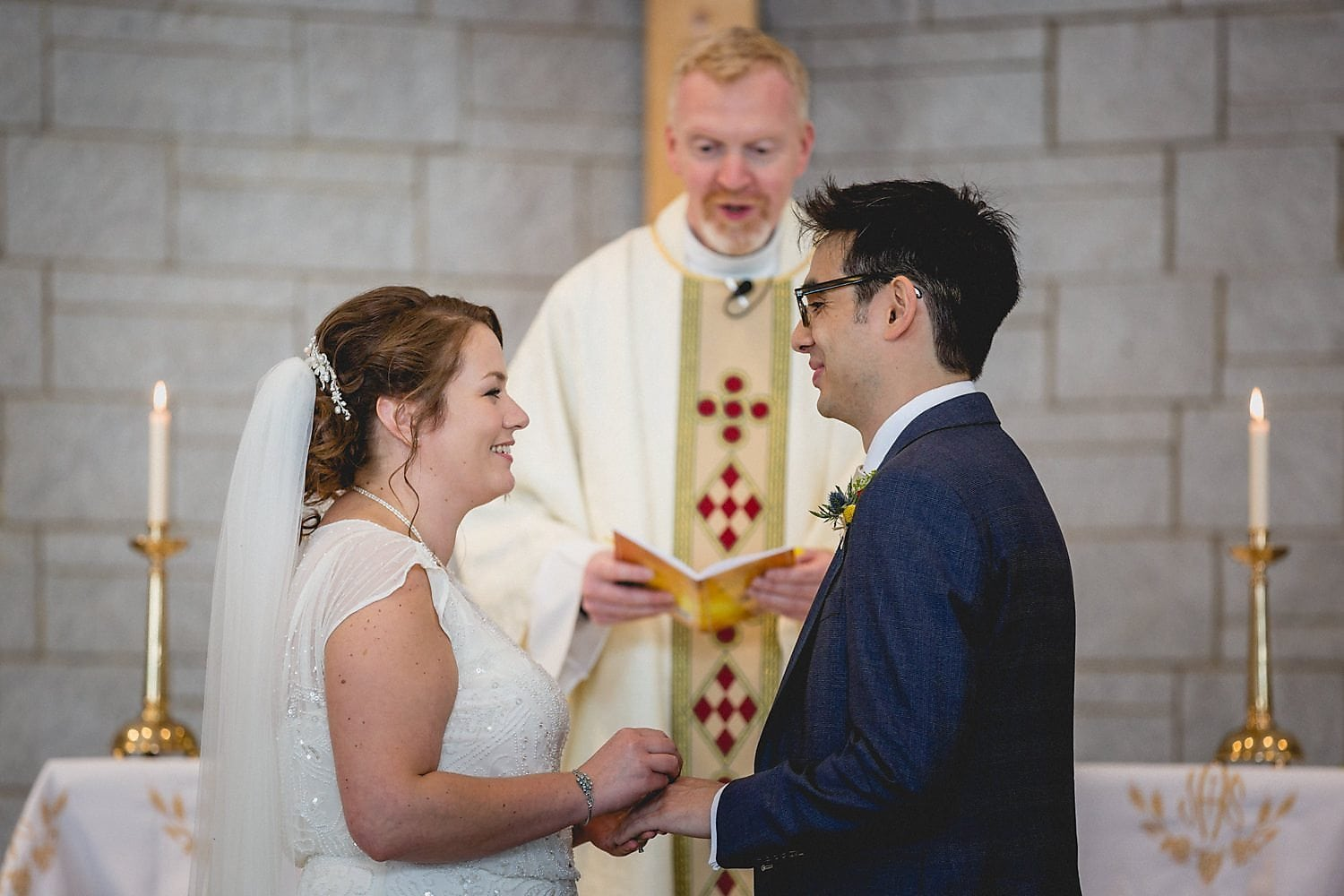 The priest conducts the ceremony as the couple smile at each other