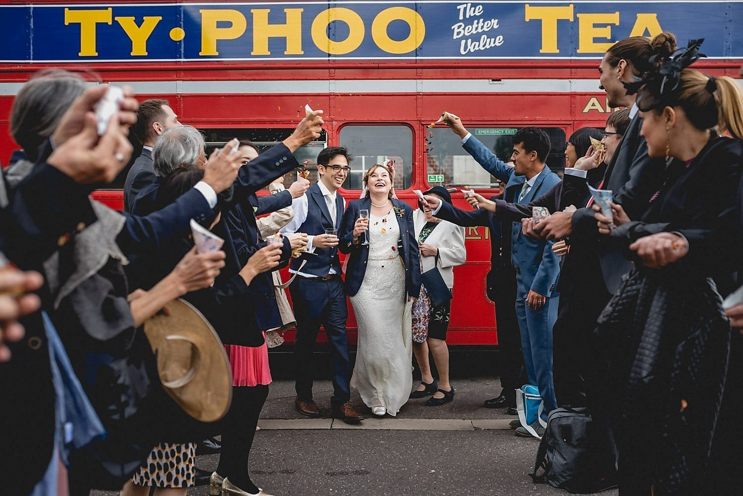 Bride and groom start the confetti line in front of the red bus