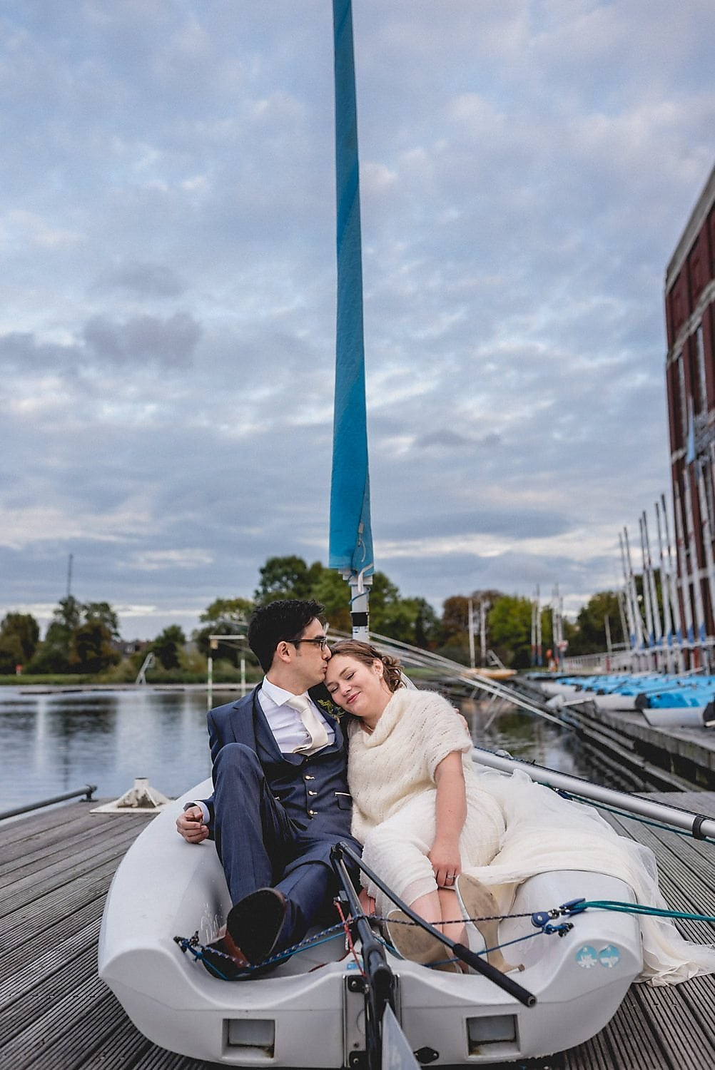 Bride and Groom sit in a sail boat on the jetty at the London West Reservoir Centre