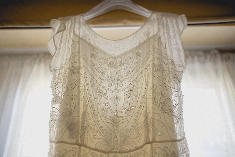 Bride's beaded dress hangs at the window