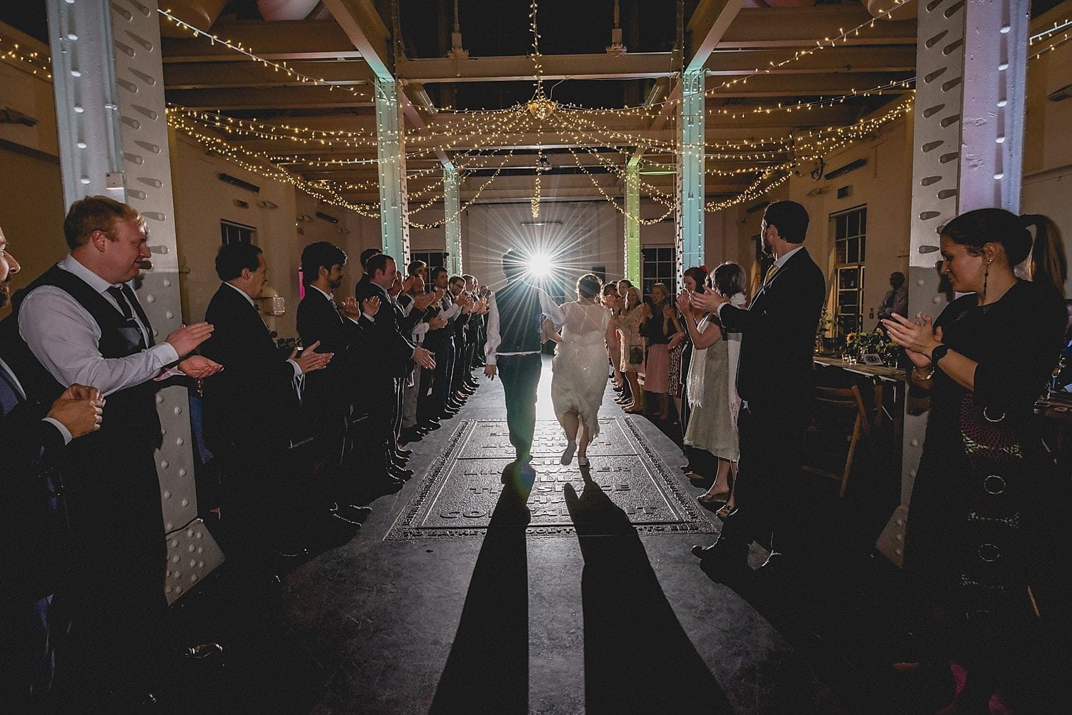 The bride and groom skip down the centre of their guests during the Ceilidh