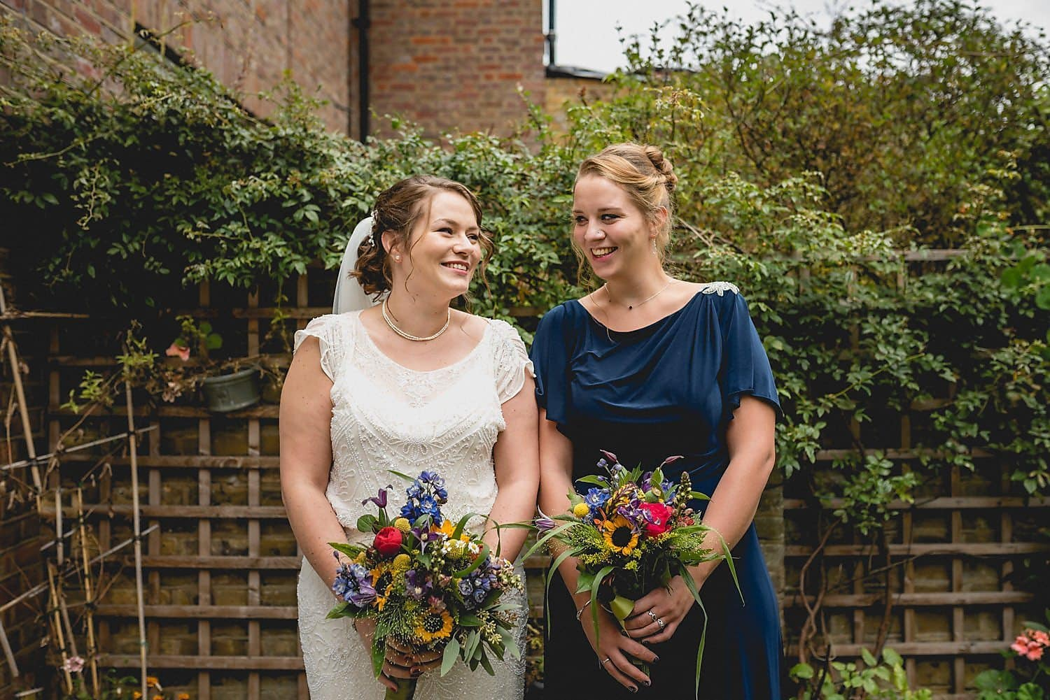 The bride and her maid of honour grin at each other outside the house before heading to the wedding