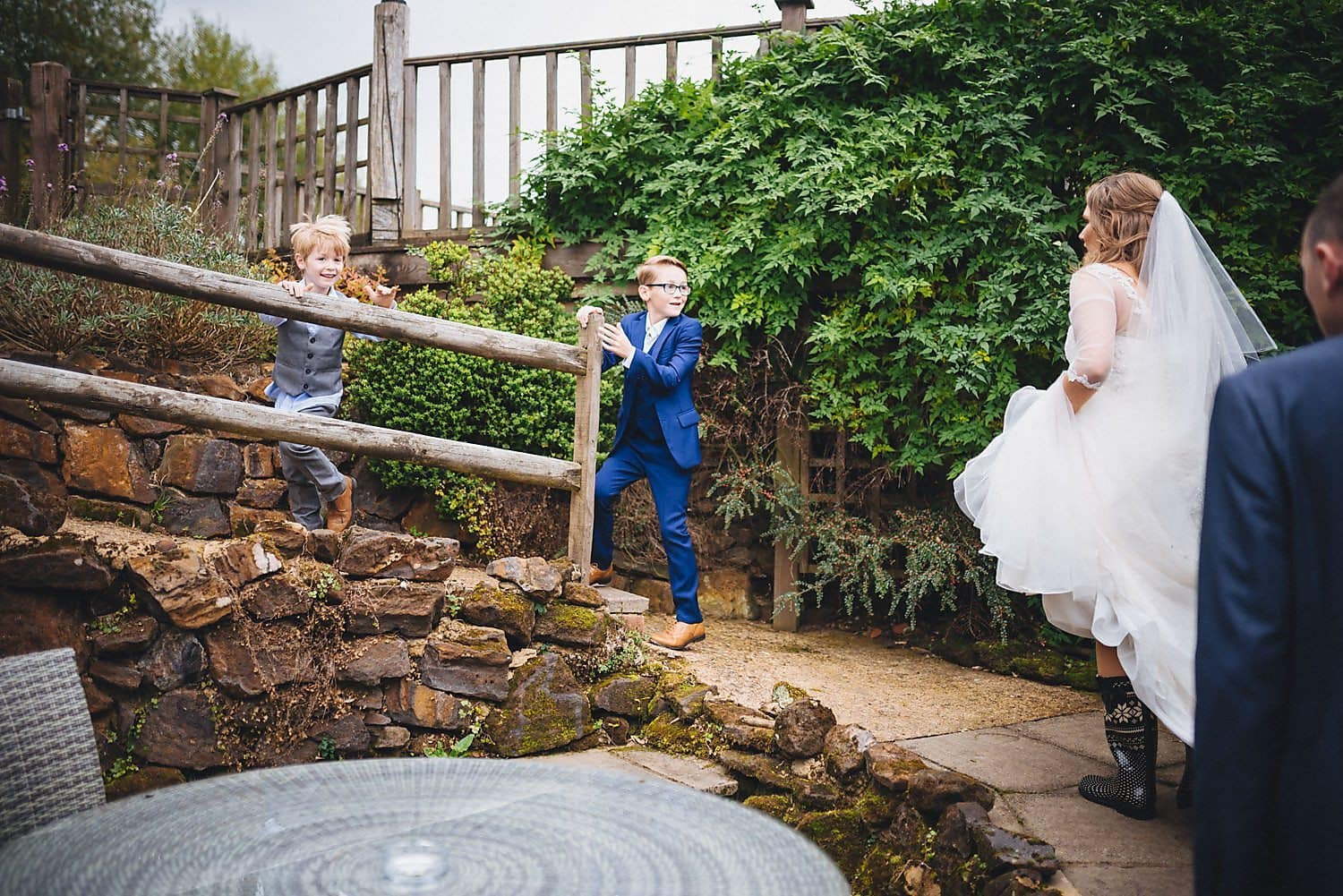 two boys running ahead of the bride and groom up the ramp at Coltsford Mill
