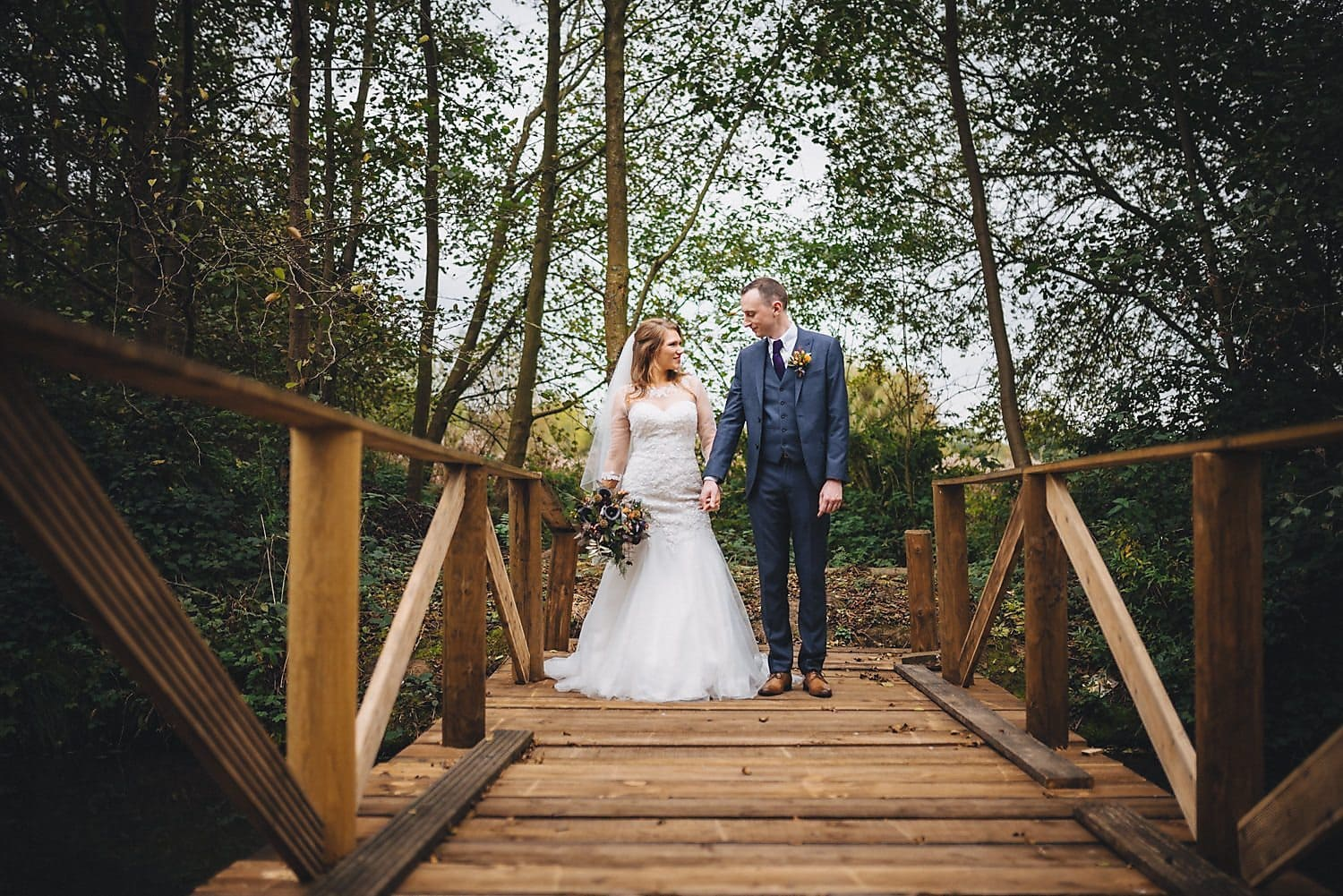 Bride and groom standing at the end of the bridge at their Coltsford Mill Wedding