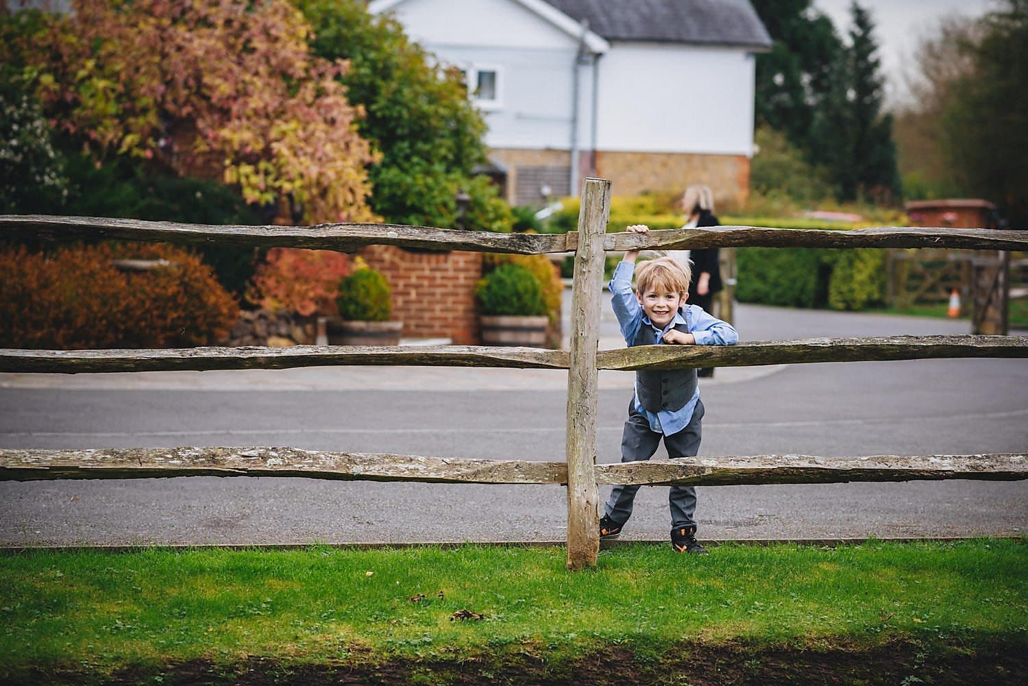 A boy looking through the fence at a wedding