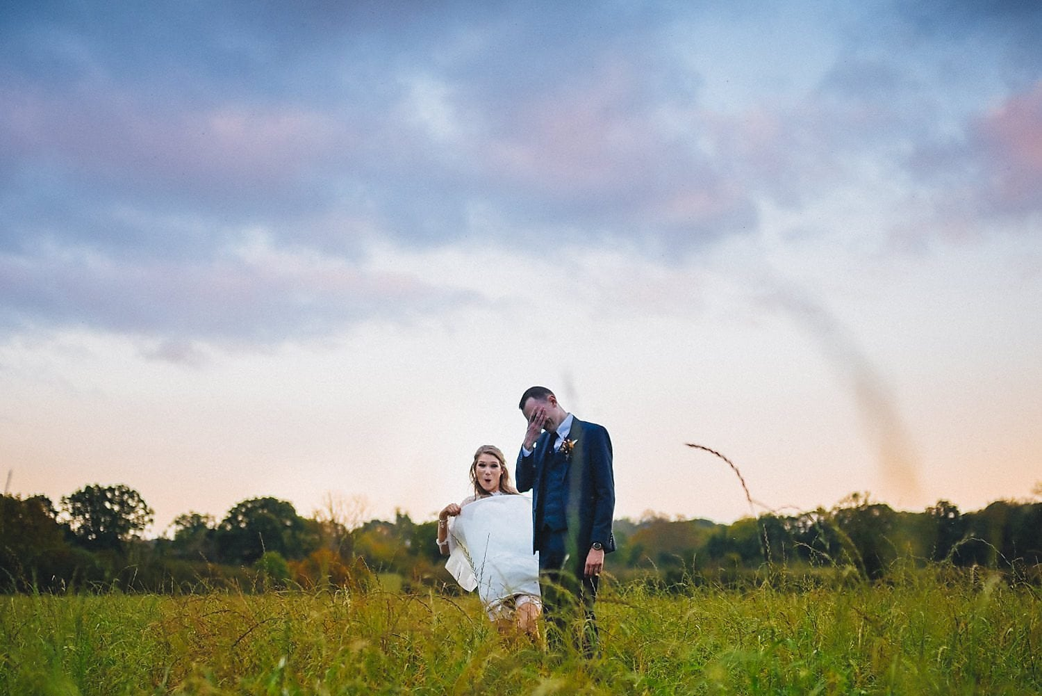 Bride and groom pose in a field at twilight. Bride jokingly lifts her dress while groom laughs and looks embarrassed.