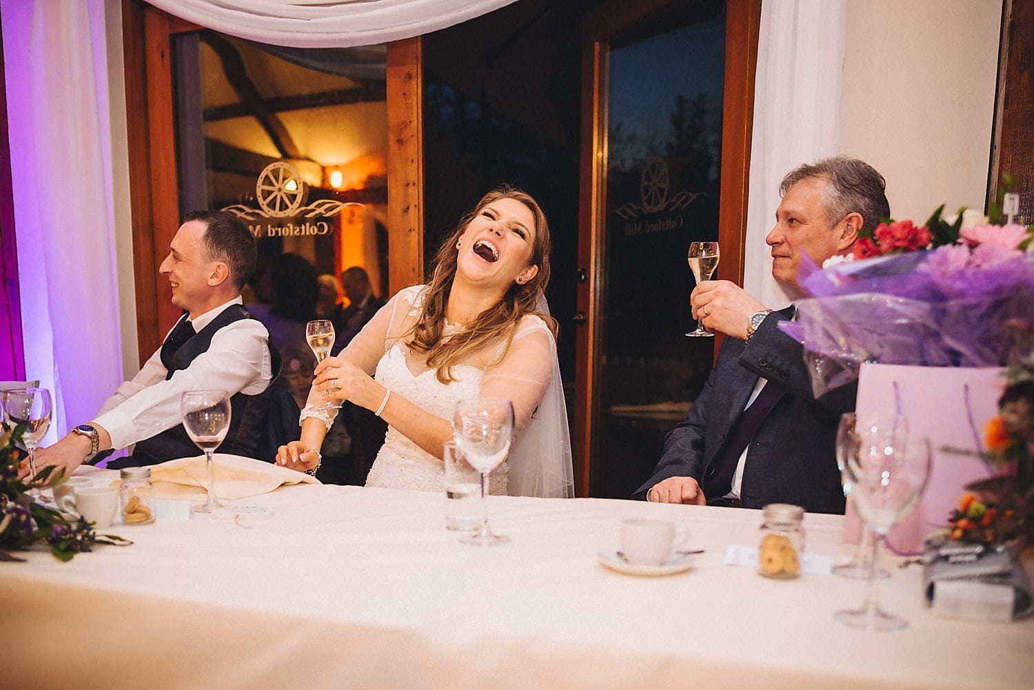 Bride laughing out loud at the wedding speeches