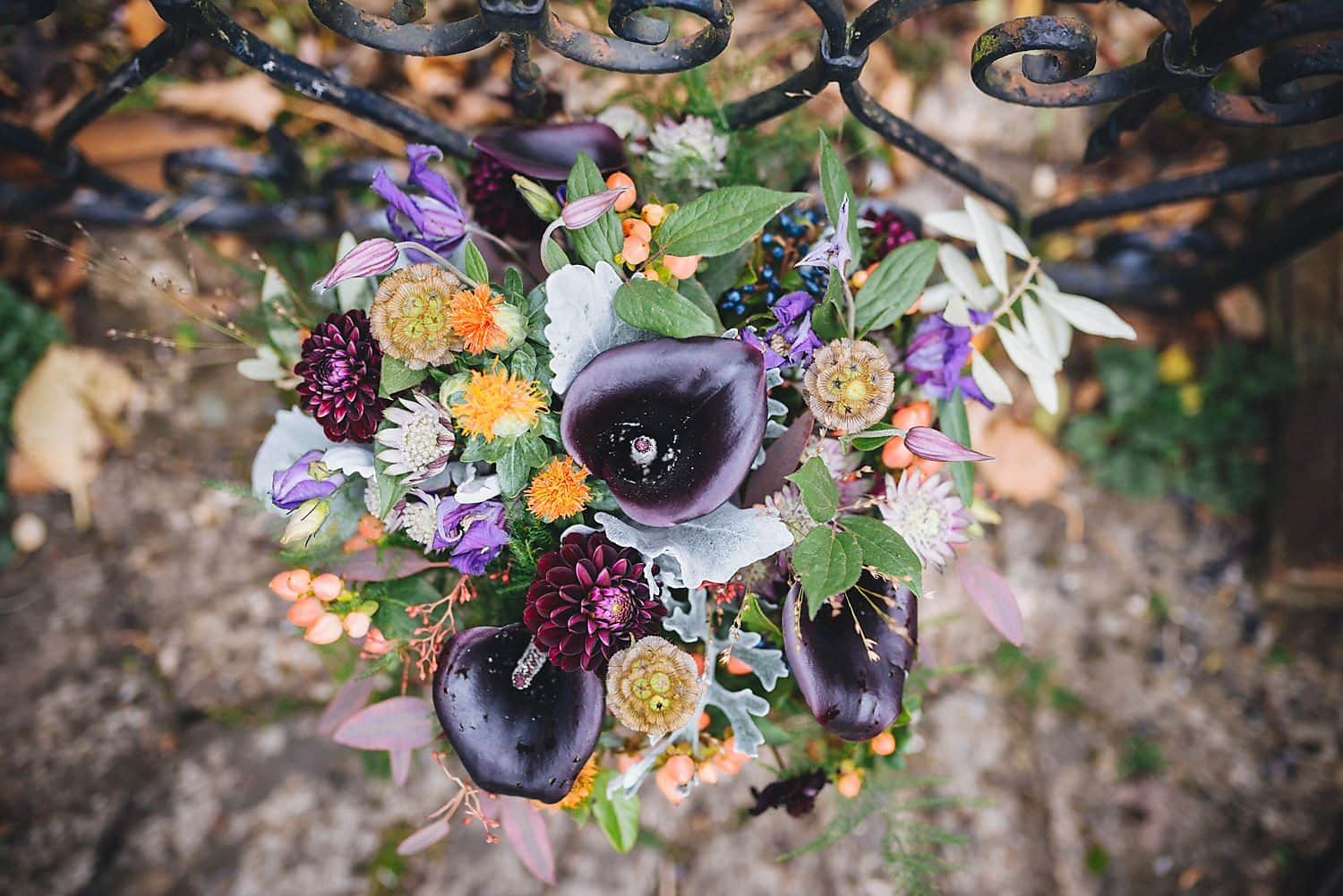 Bridal bouquet from above, featuring rich autumnal shades of deep purple, berry red and orange
