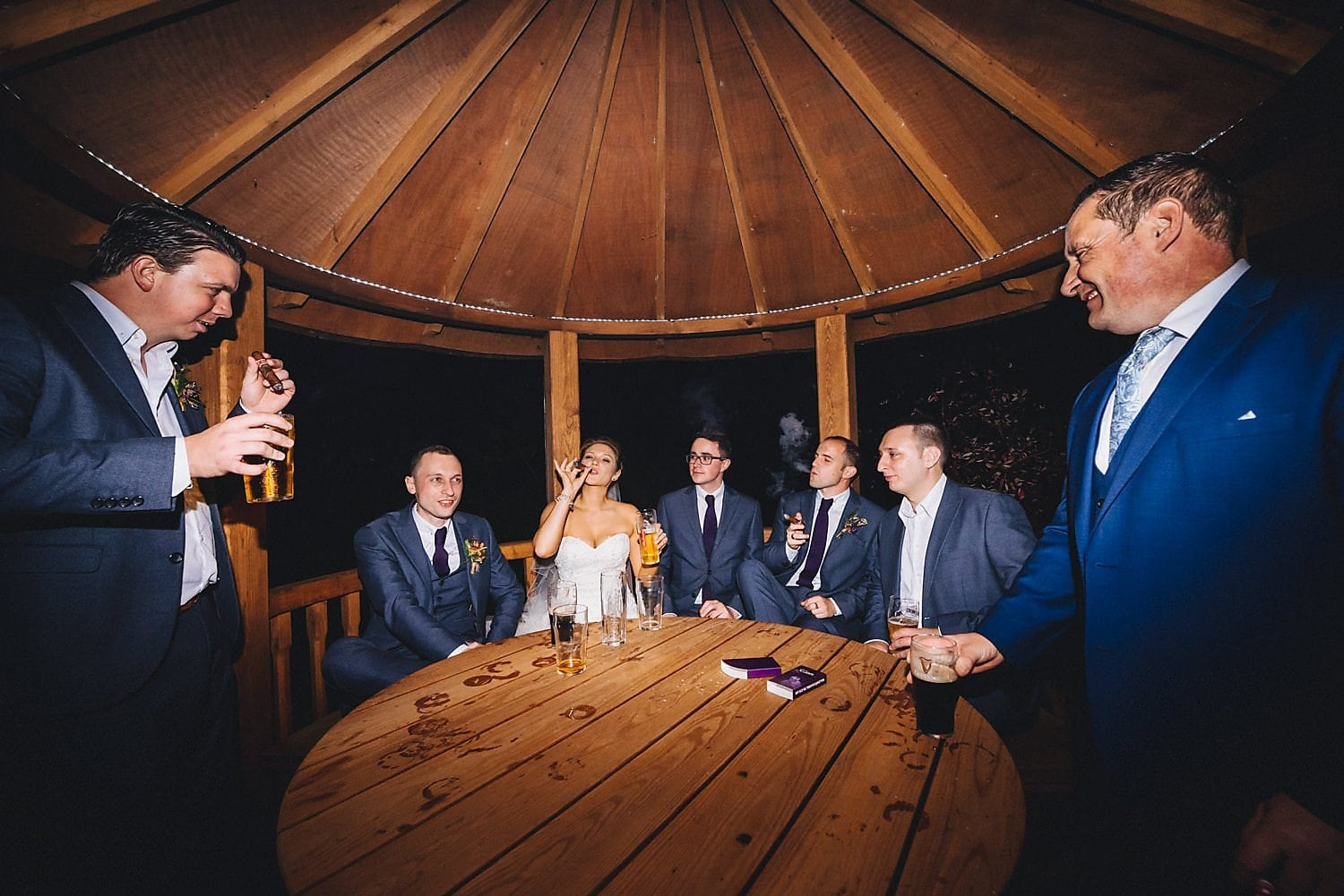 Bride, groom and groomsmen enjoy a celebratory cigar at the wedding party