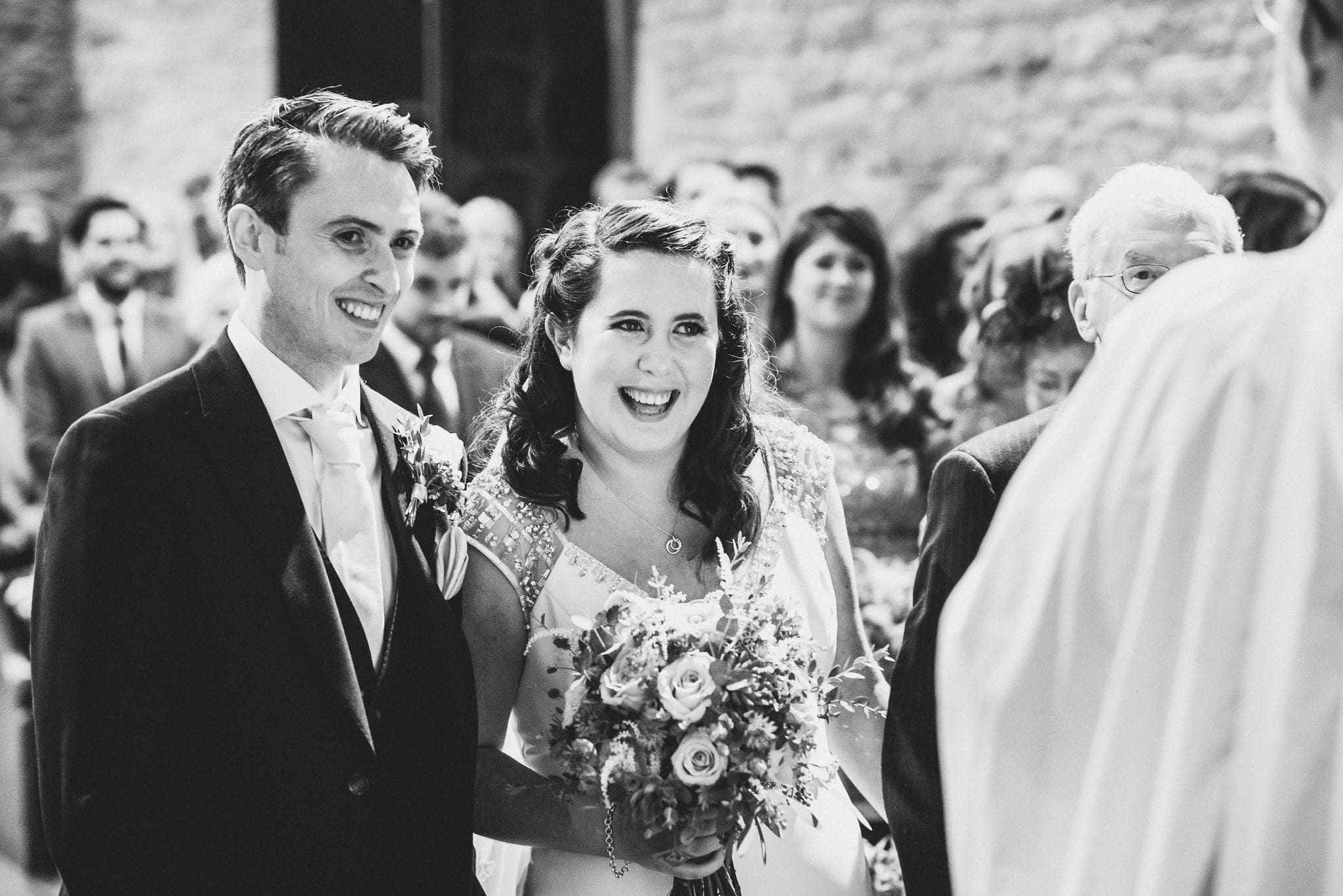 Black and white shot of the couple smiling together at the altar