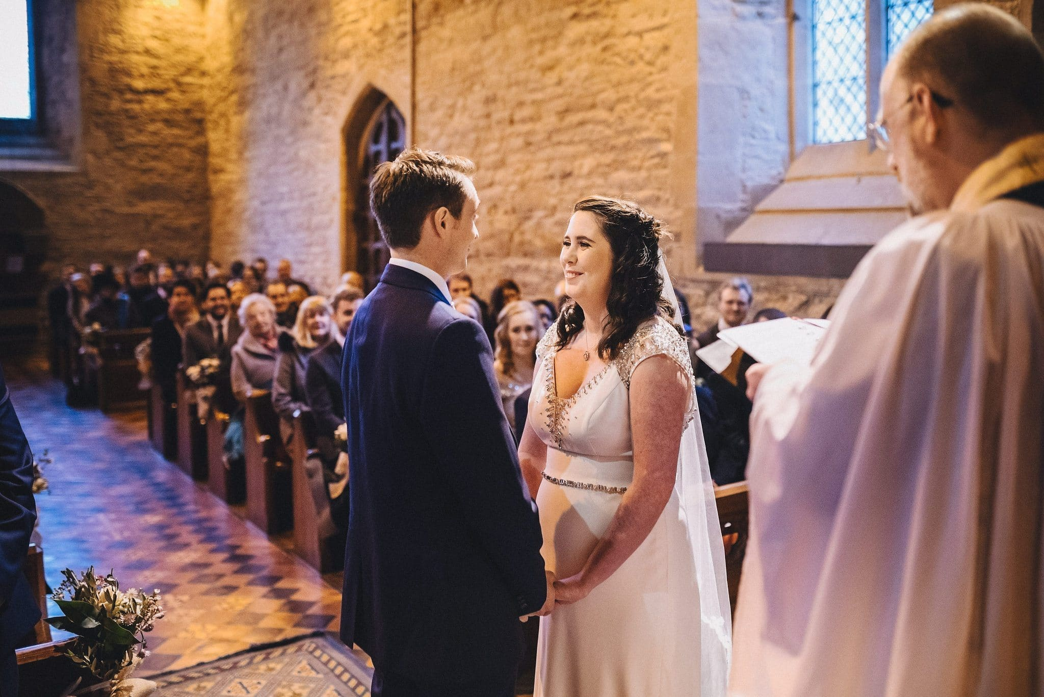 Bride and groom hold hands as they say their vows