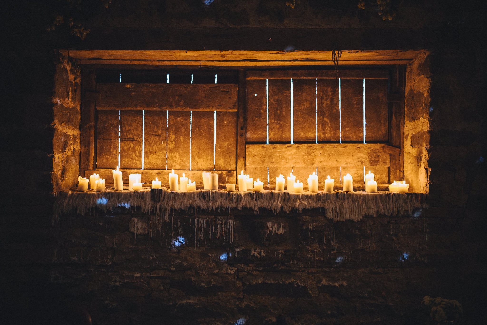Row of candles on a window ledge with wax dripping down