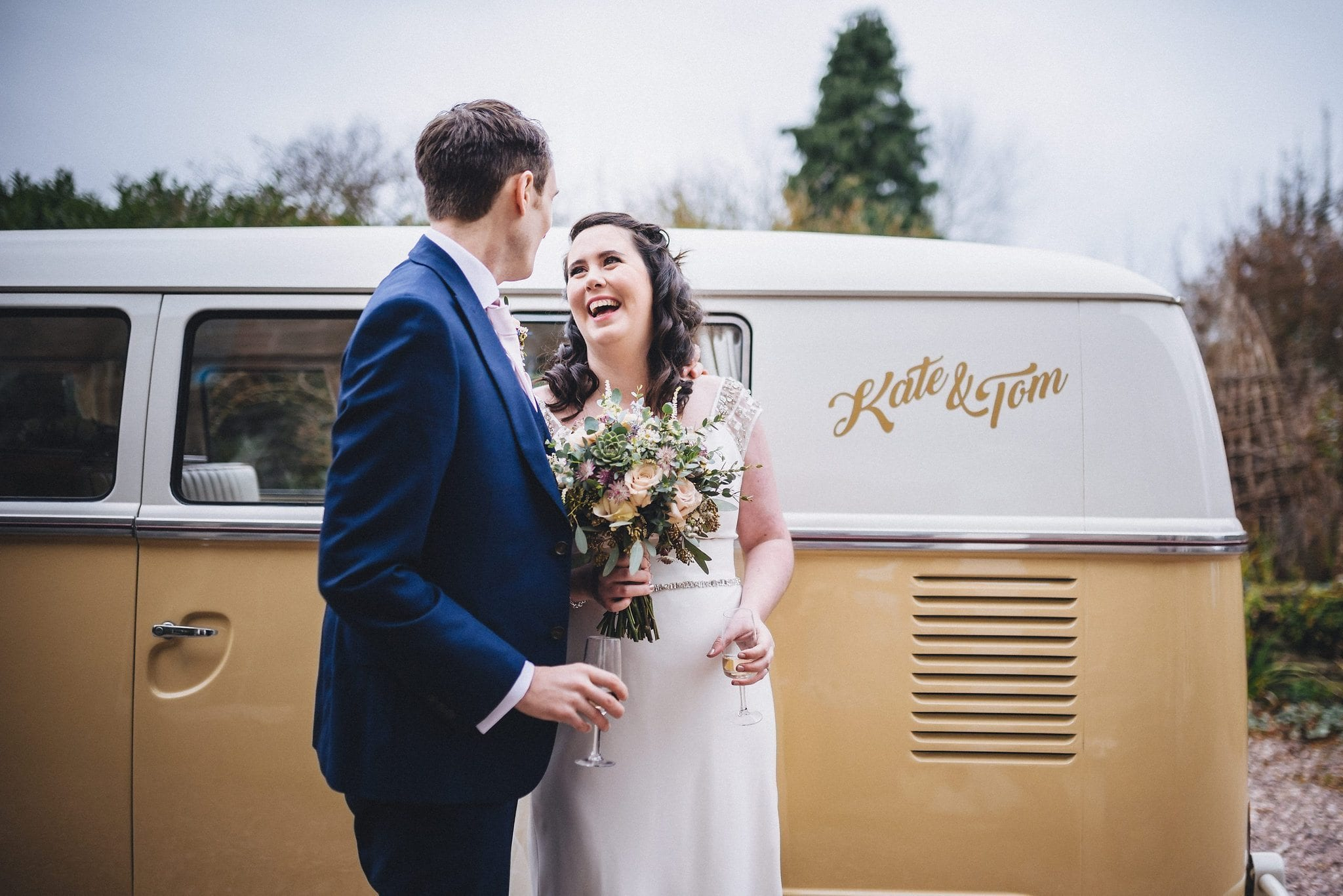 Bride and groom laugh together next to their personalised VW camper van