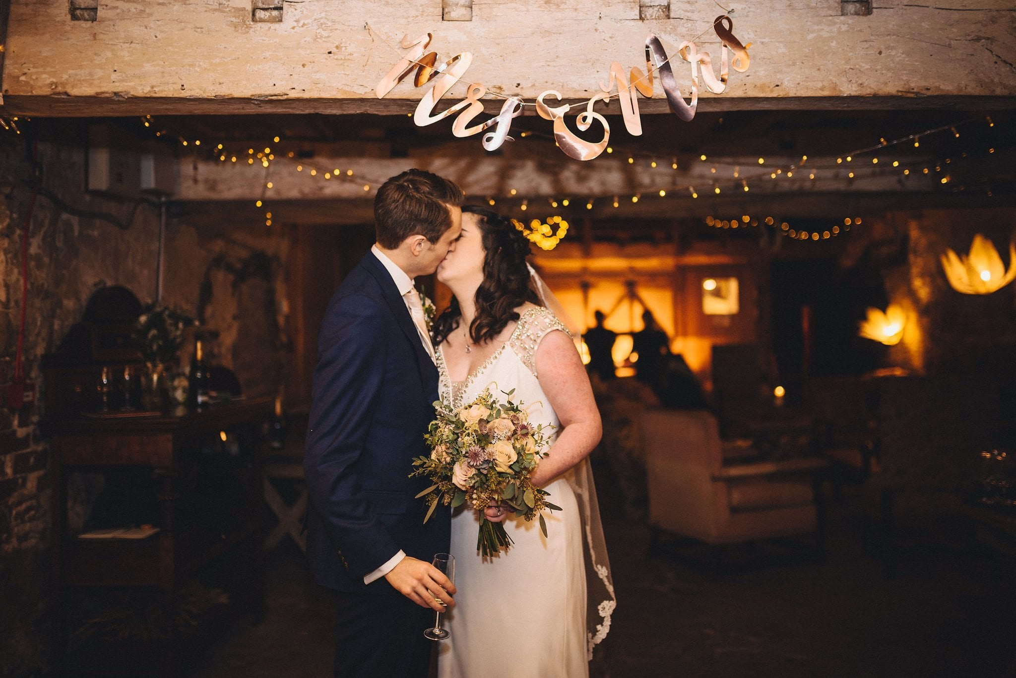 Bride and groom kiss under a Mrs and Mrs sign