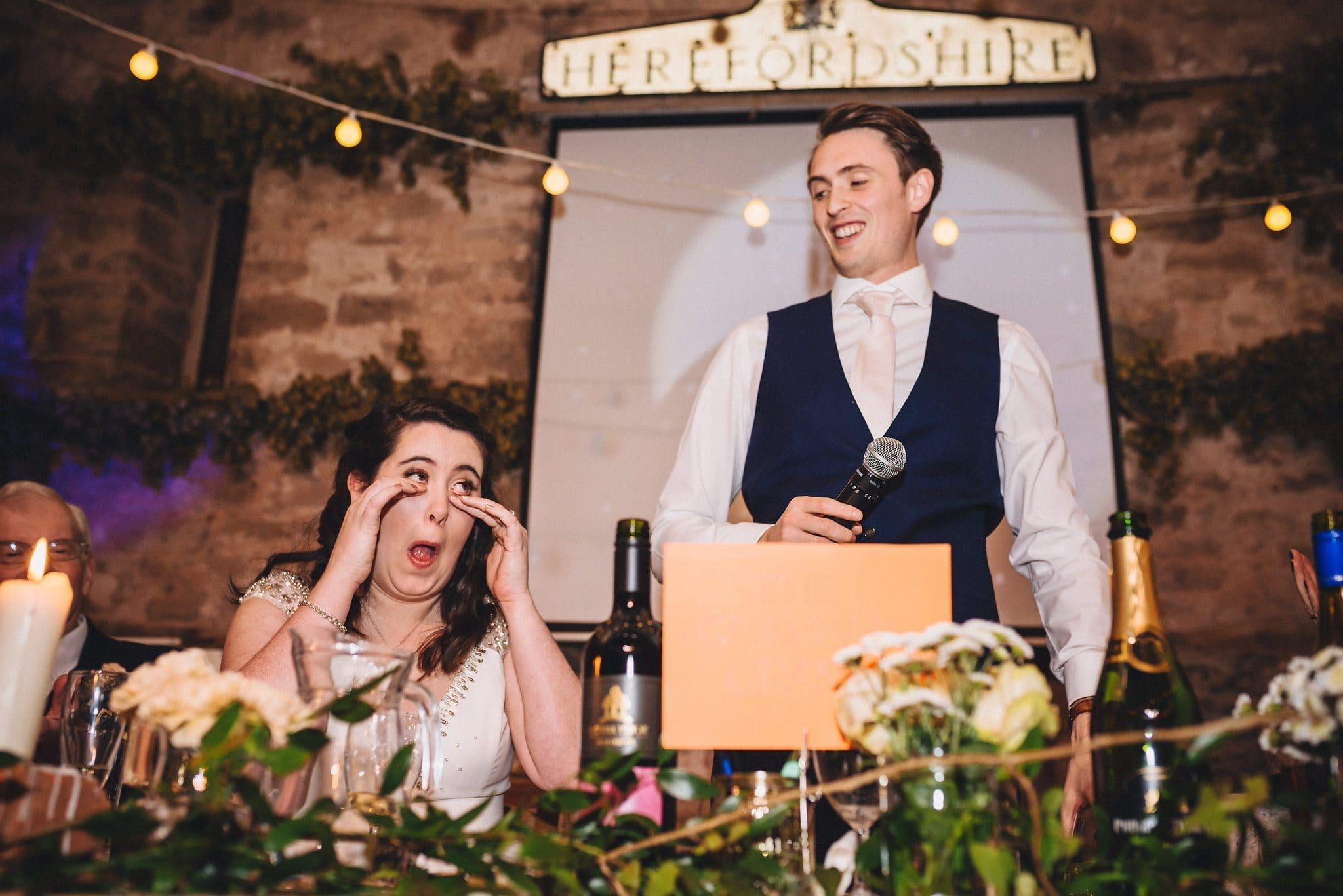 Bride wipes tears from her eyes as groom makes his speech